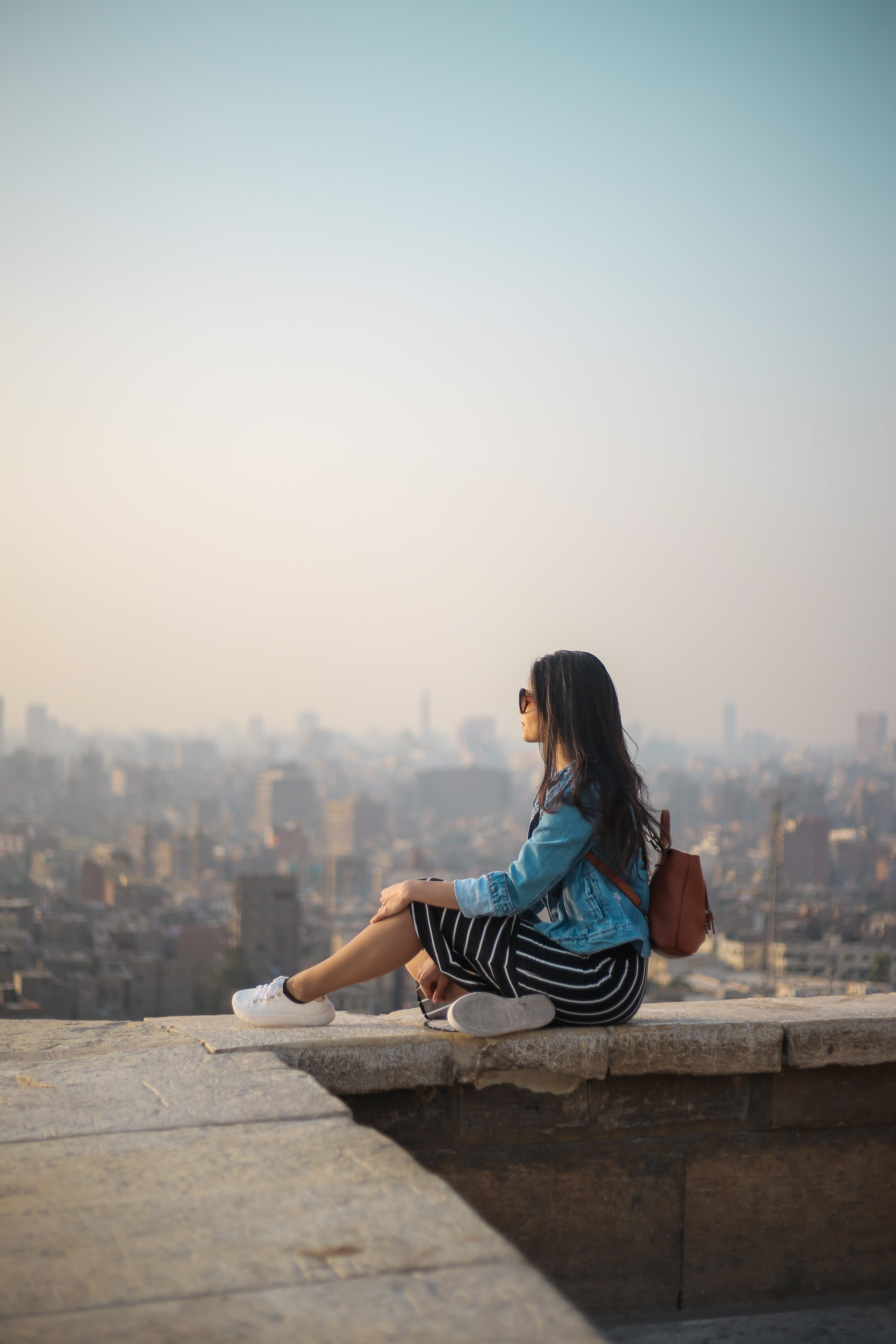 Woman Sitting on Top of Building's Edge