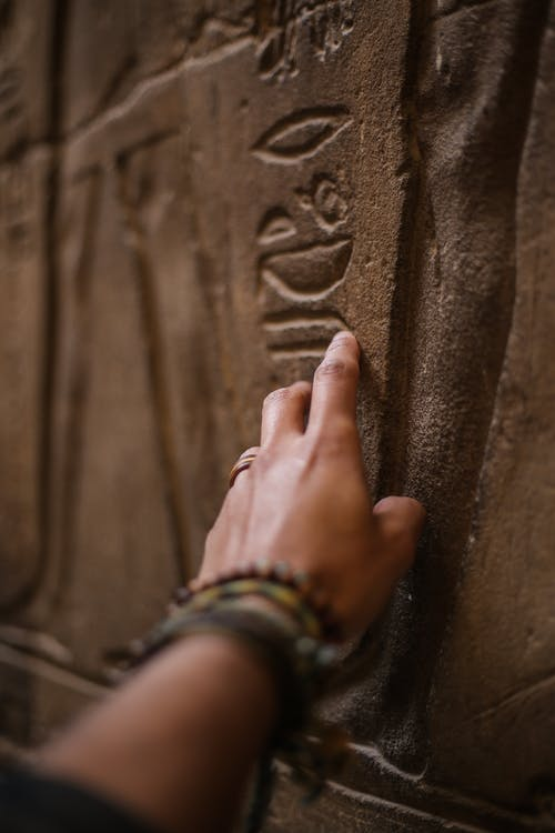 Close-Up Photo of Person Touching Inscribed Wall