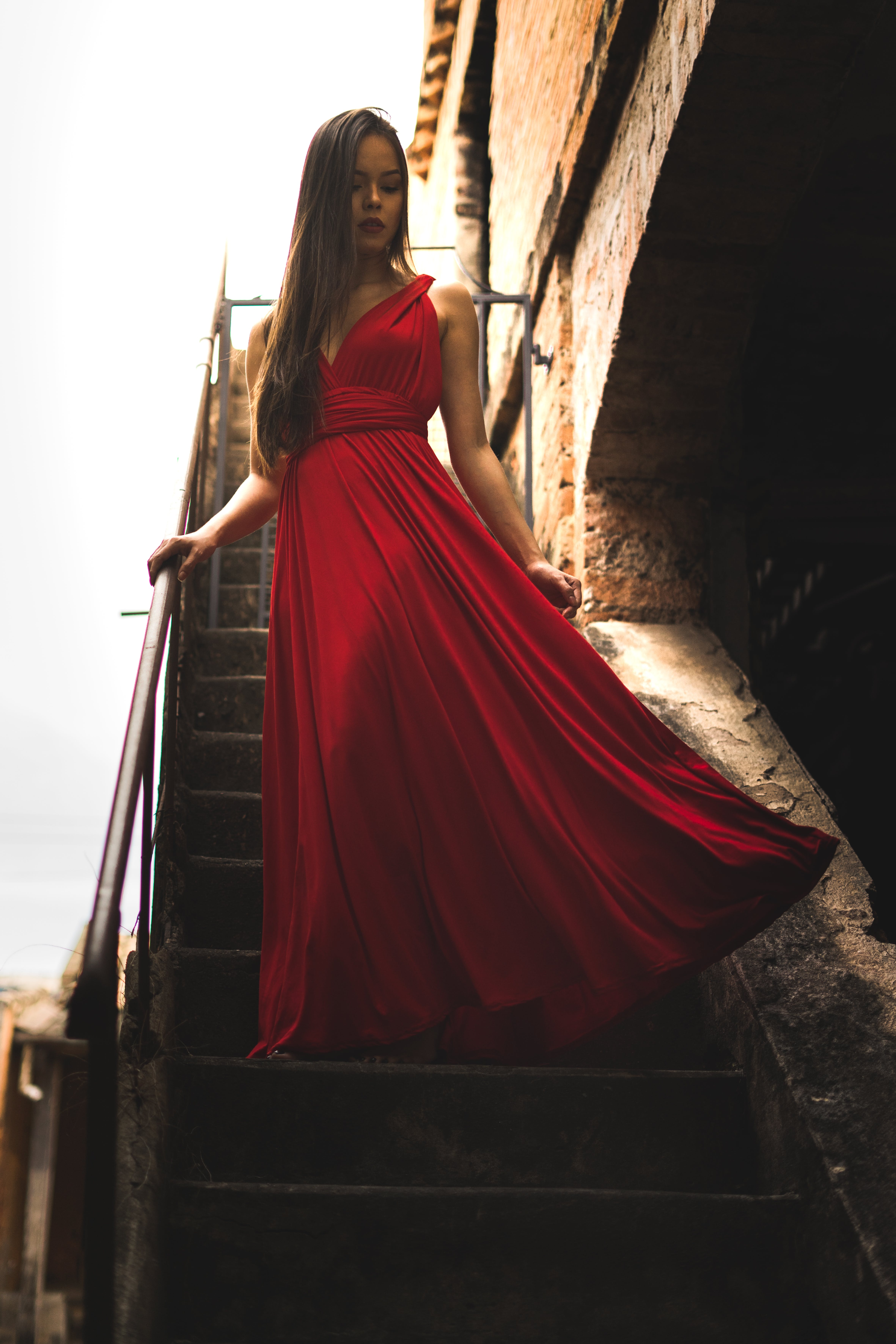 Woman Wearing Red Dress Standing on Staircase