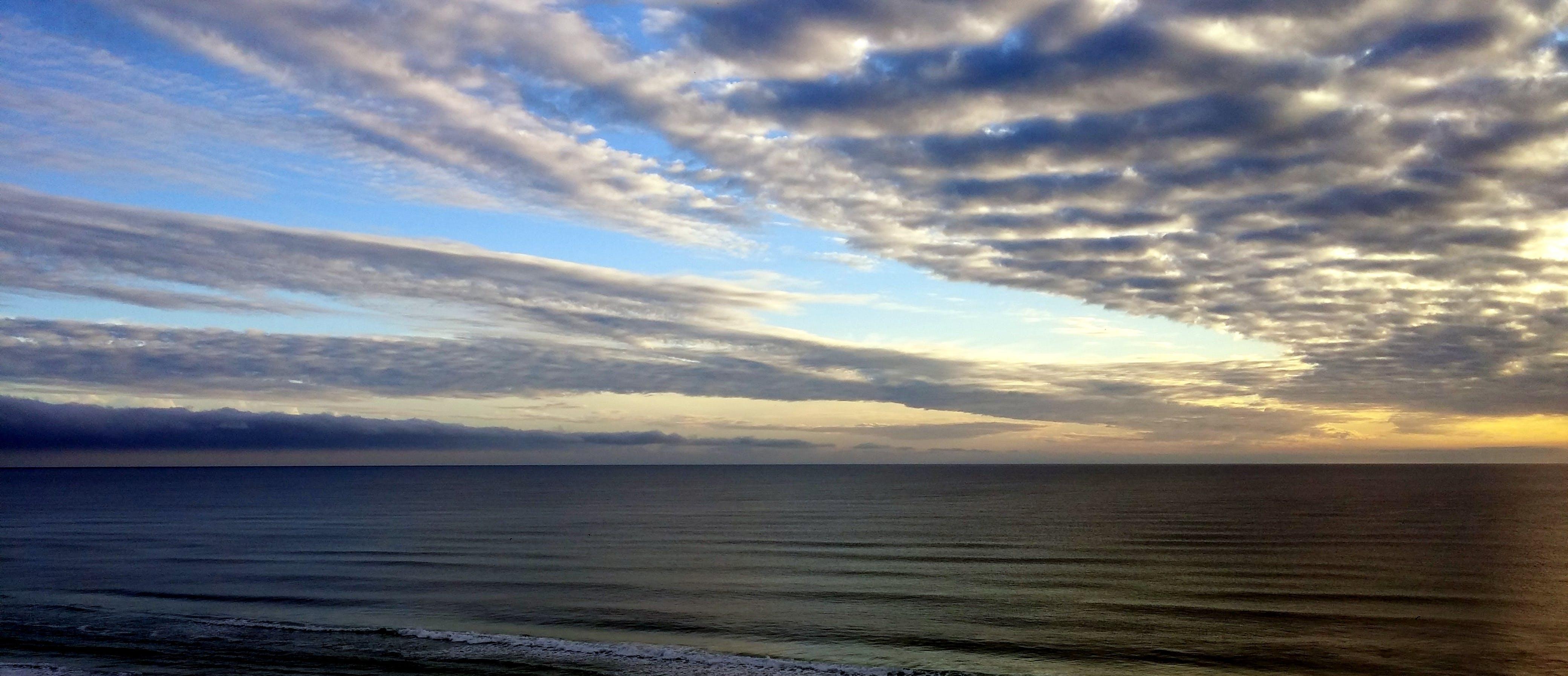 White Sky Under Blue Sea during Dawn