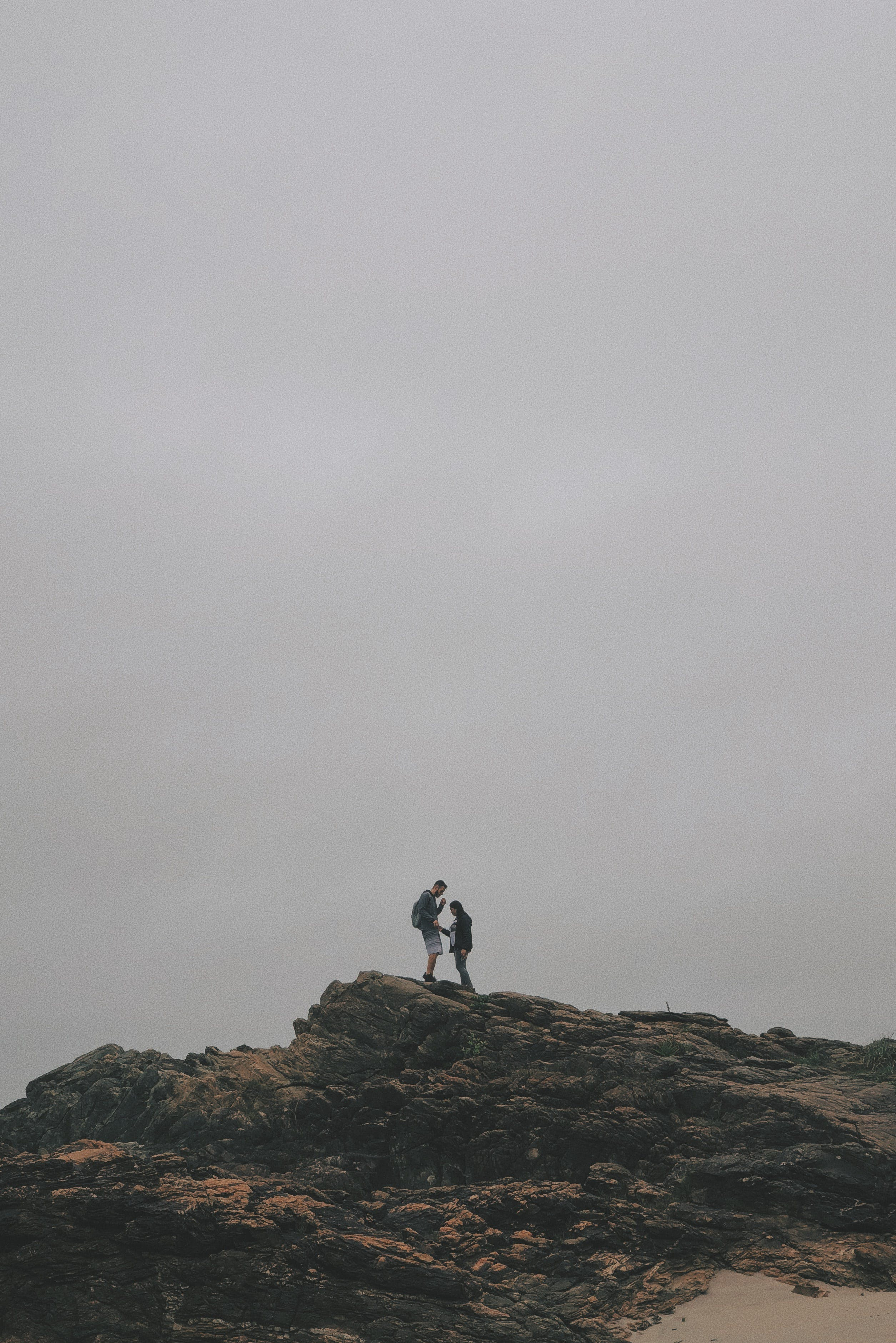 Man and Woman Standing on Rock Under White Sky