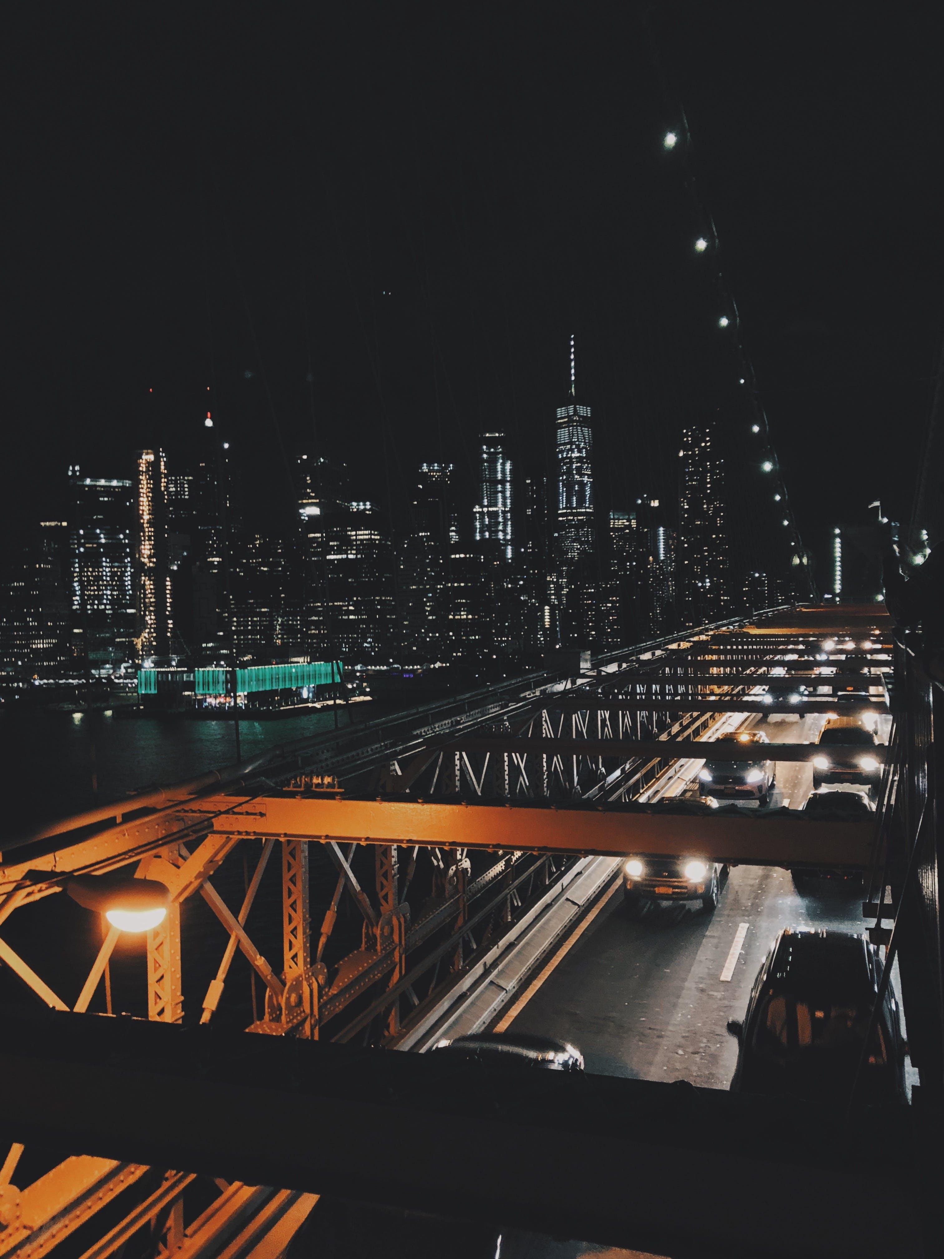 Vehicles on Bridge Under Black Sky