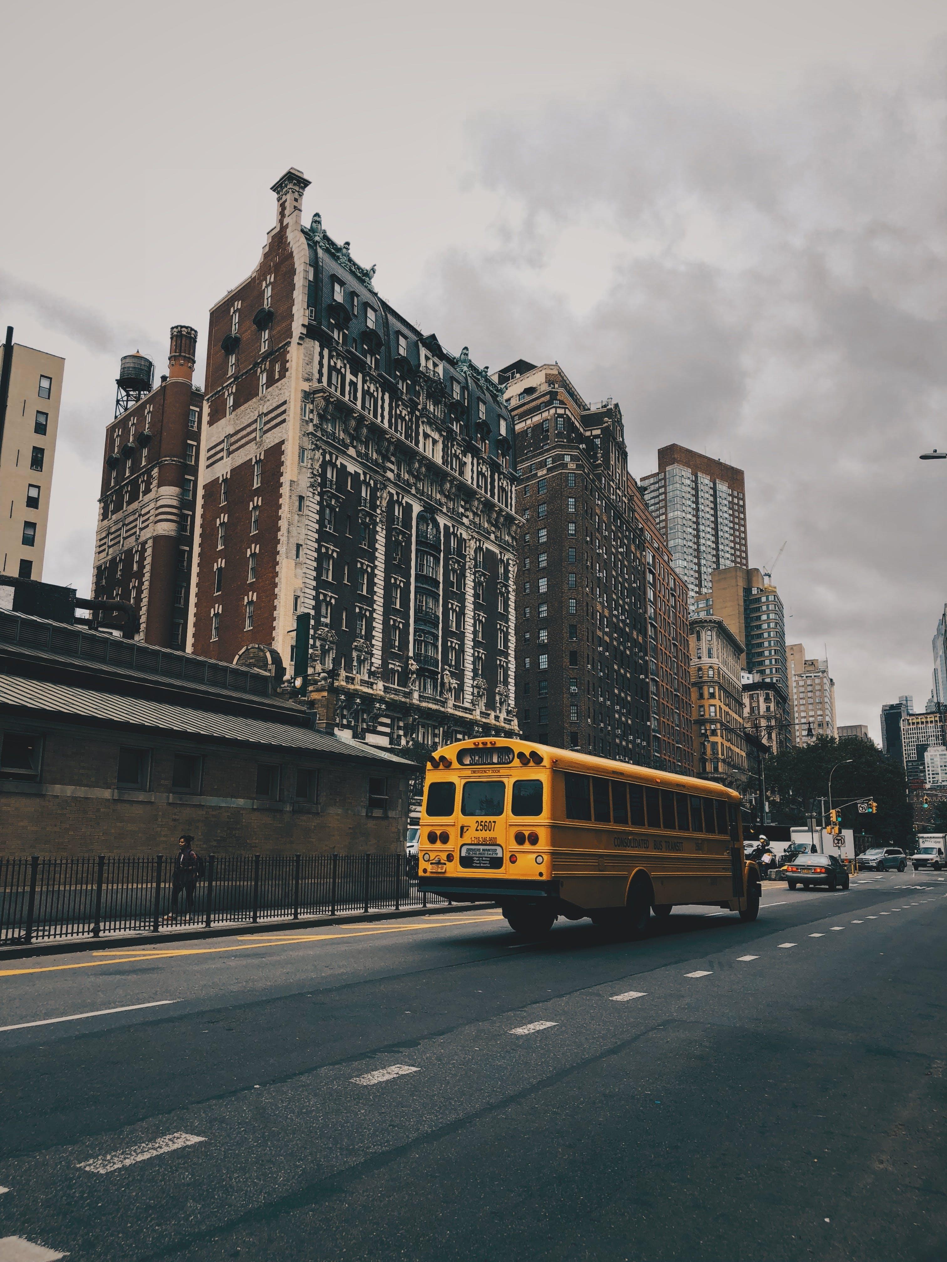 Photos gratuites de architecture, asphalte, bâtiments, bus de l'école