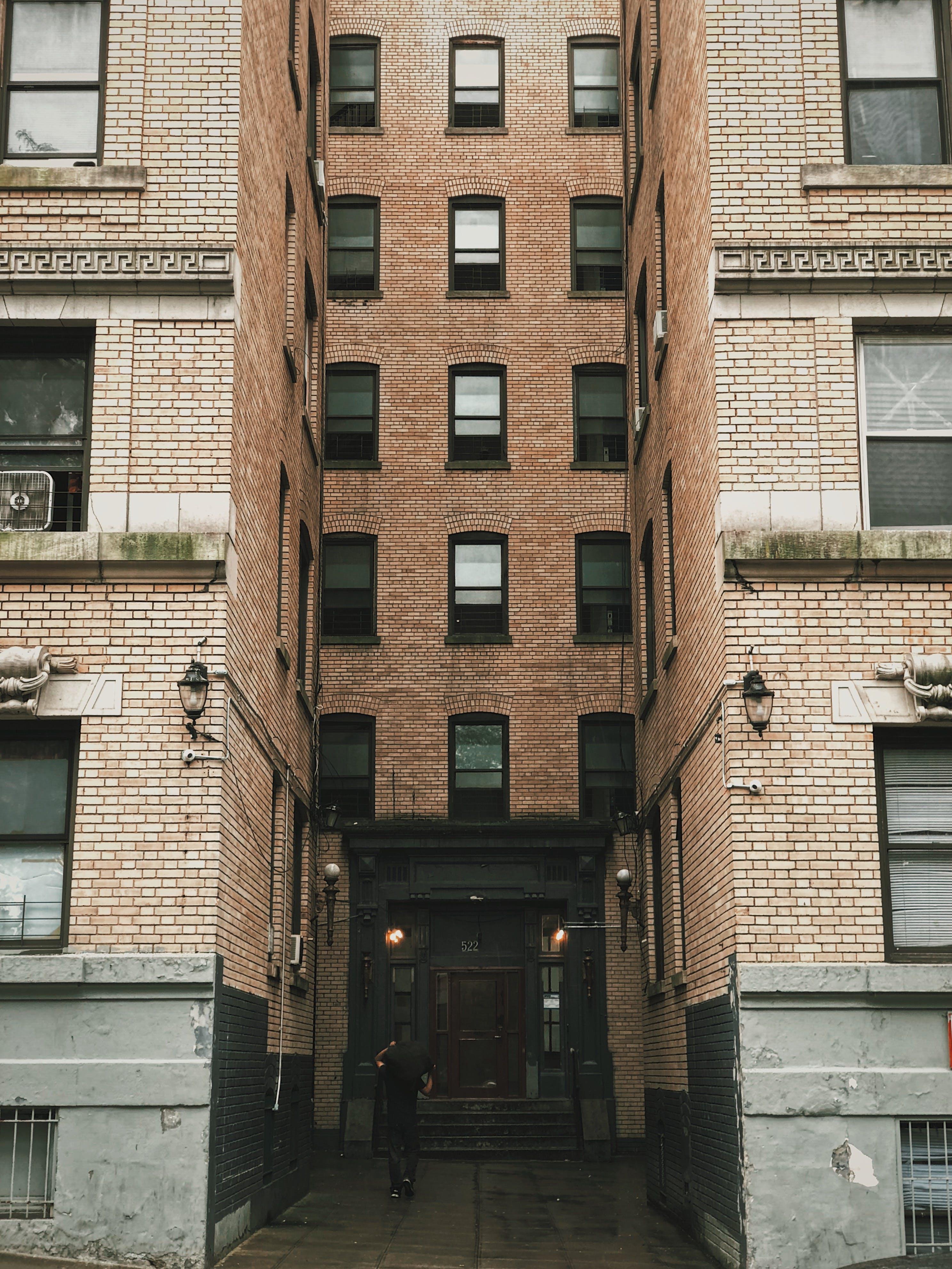 Person Standing Between Brown Concrete Building