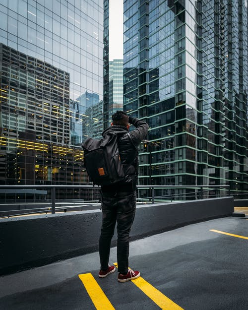 Photo of Man Standing Near High-rise Building