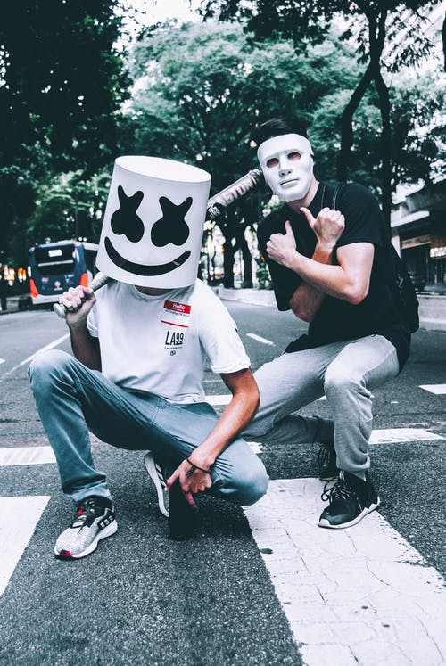 Photo of Two Men in Masks Squat Posing