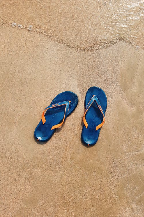 Top View Photo of Slippers On Seashore