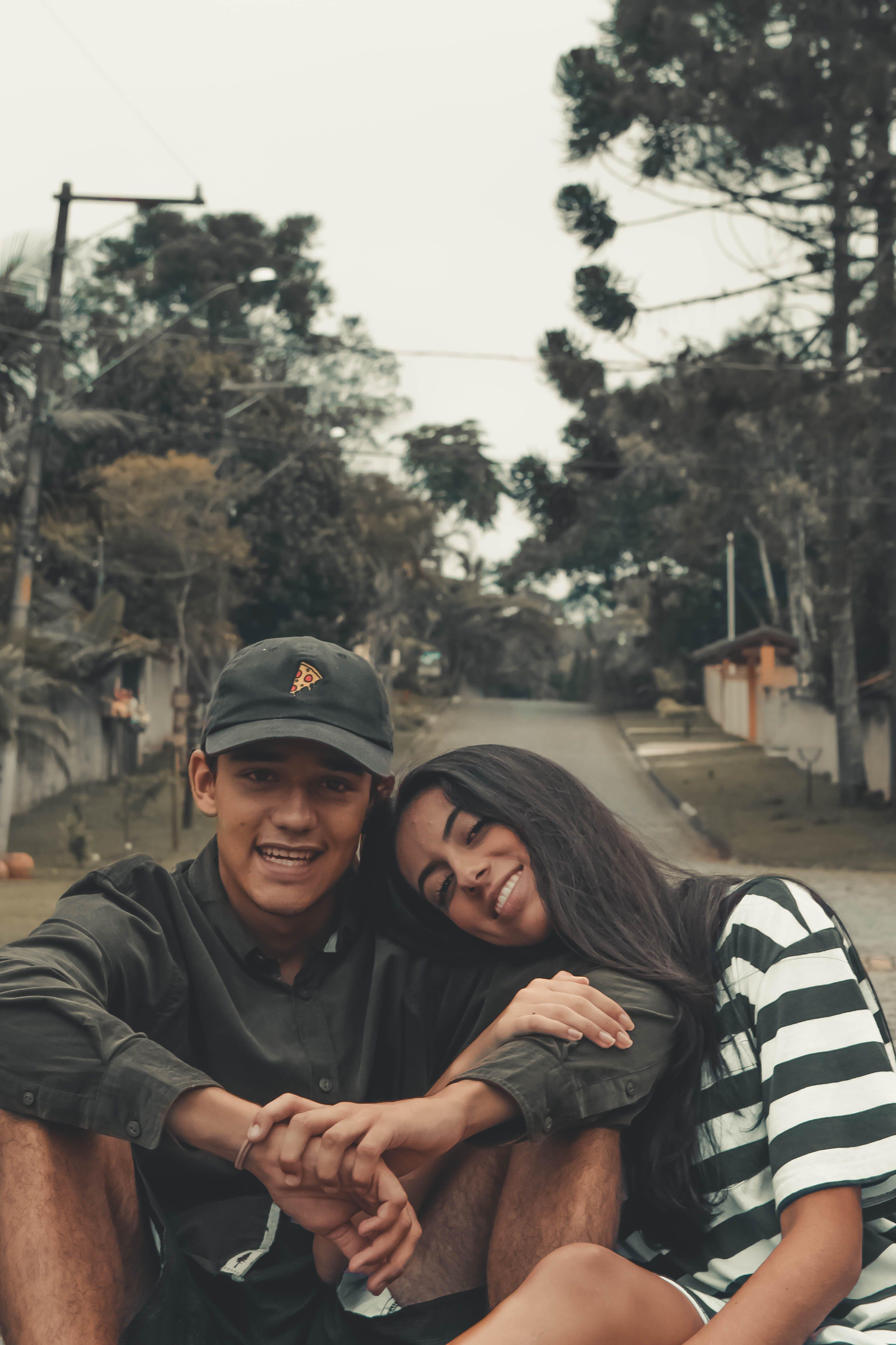 Photo of Man Wearing Cap Sitting Beside Woman