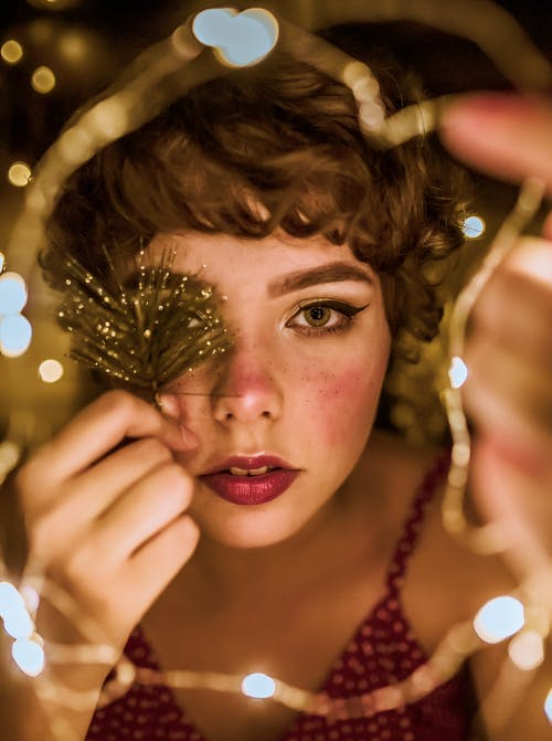 Selective Focus Photography of Woman Surrounded by String Lights