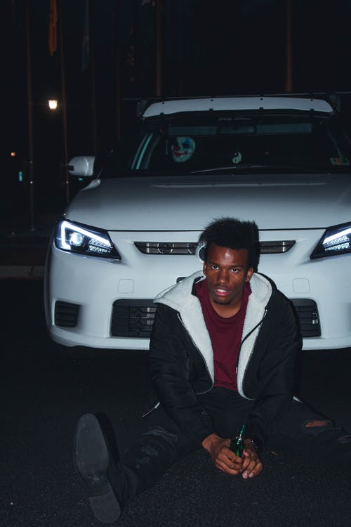 Man Sitting on Road While Leaning on White Vehicle at Night