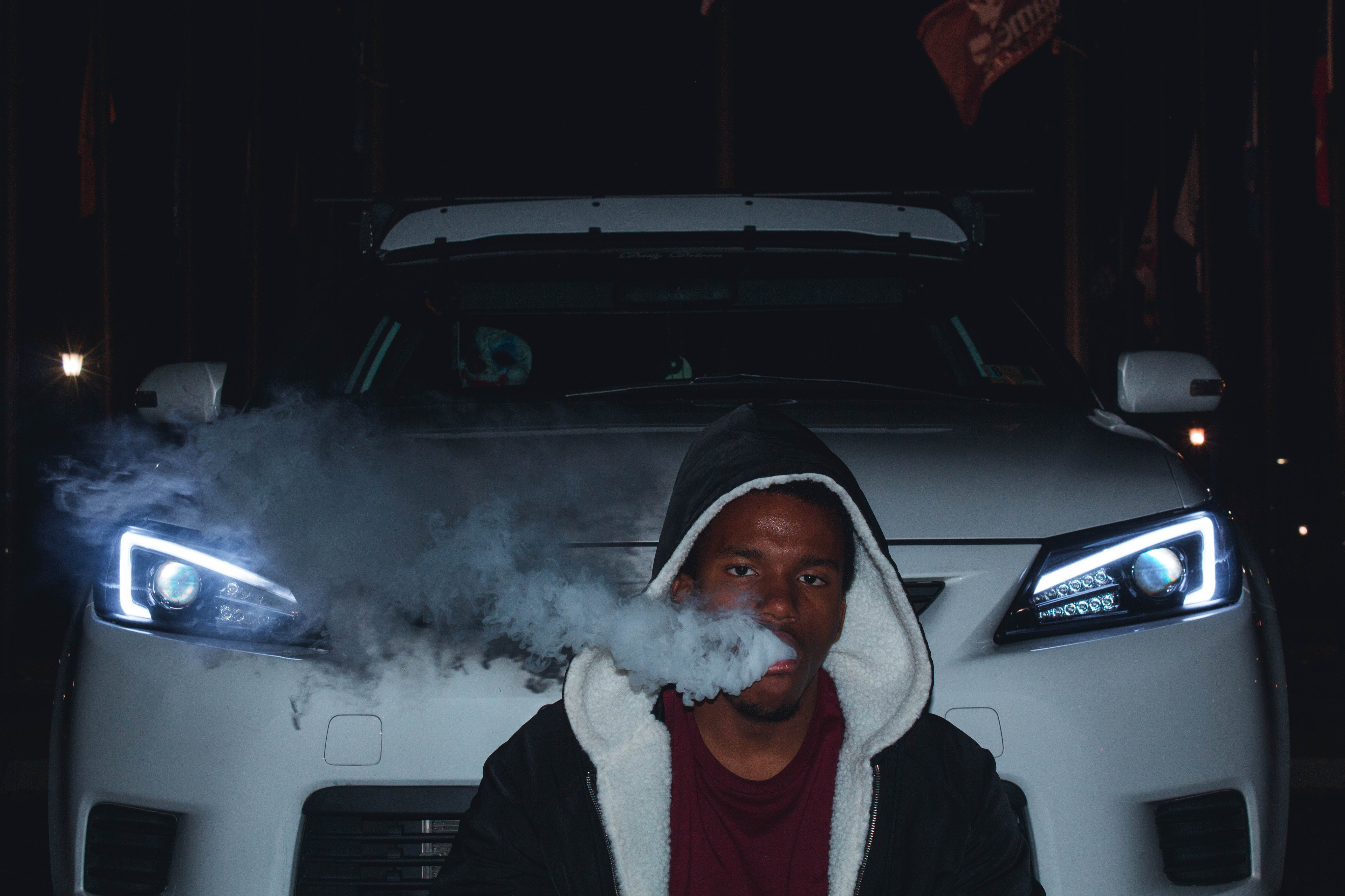 Photo of Man Smoking In Front Of Car