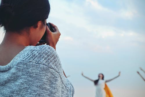 Woman Taking Picture of Woman Dancing Under White Sky