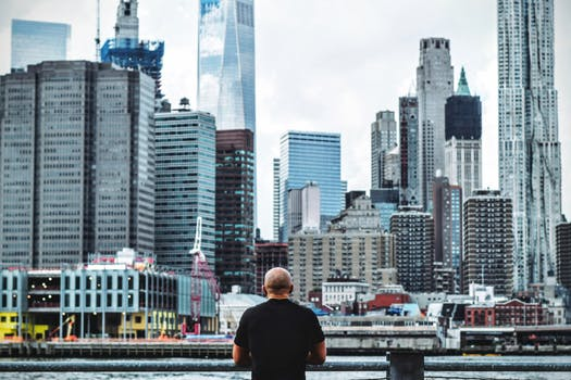 Man In Black T Shirt In Front On City Skyline During Daytime