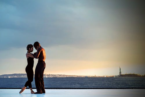 Man and Woman Dancing Near Body of Water