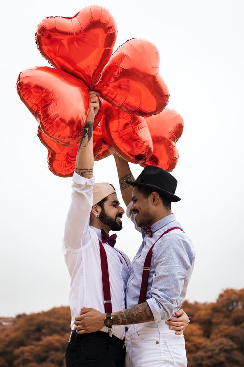 Two Men  Embracing while Holding Heart Balloons