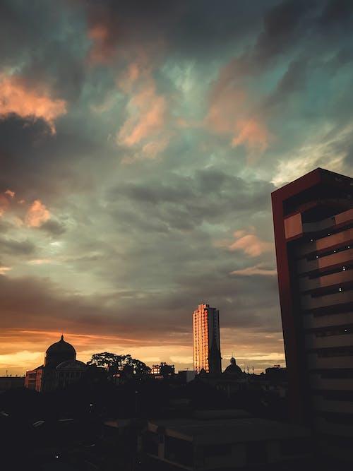 Photos gratuites de architecture, aube, bâtiments, ciel nuageux