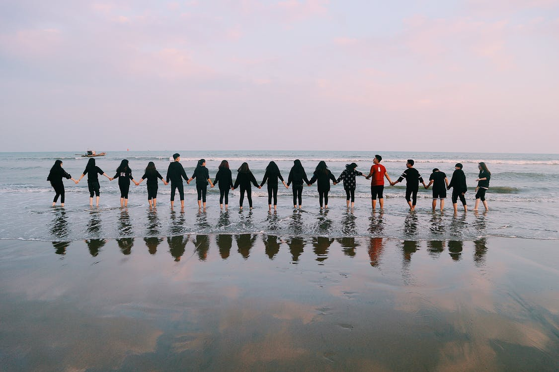 Team Holding Their Hands On Seashore