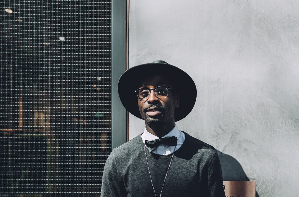 Man Wearing Hat and Bowtie in Front of Concrete Wall