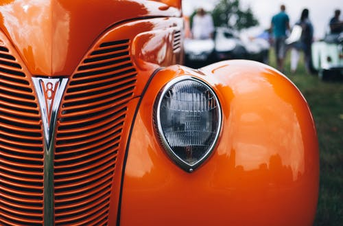 Selective Focus Photography of Classic Orange Vehicle