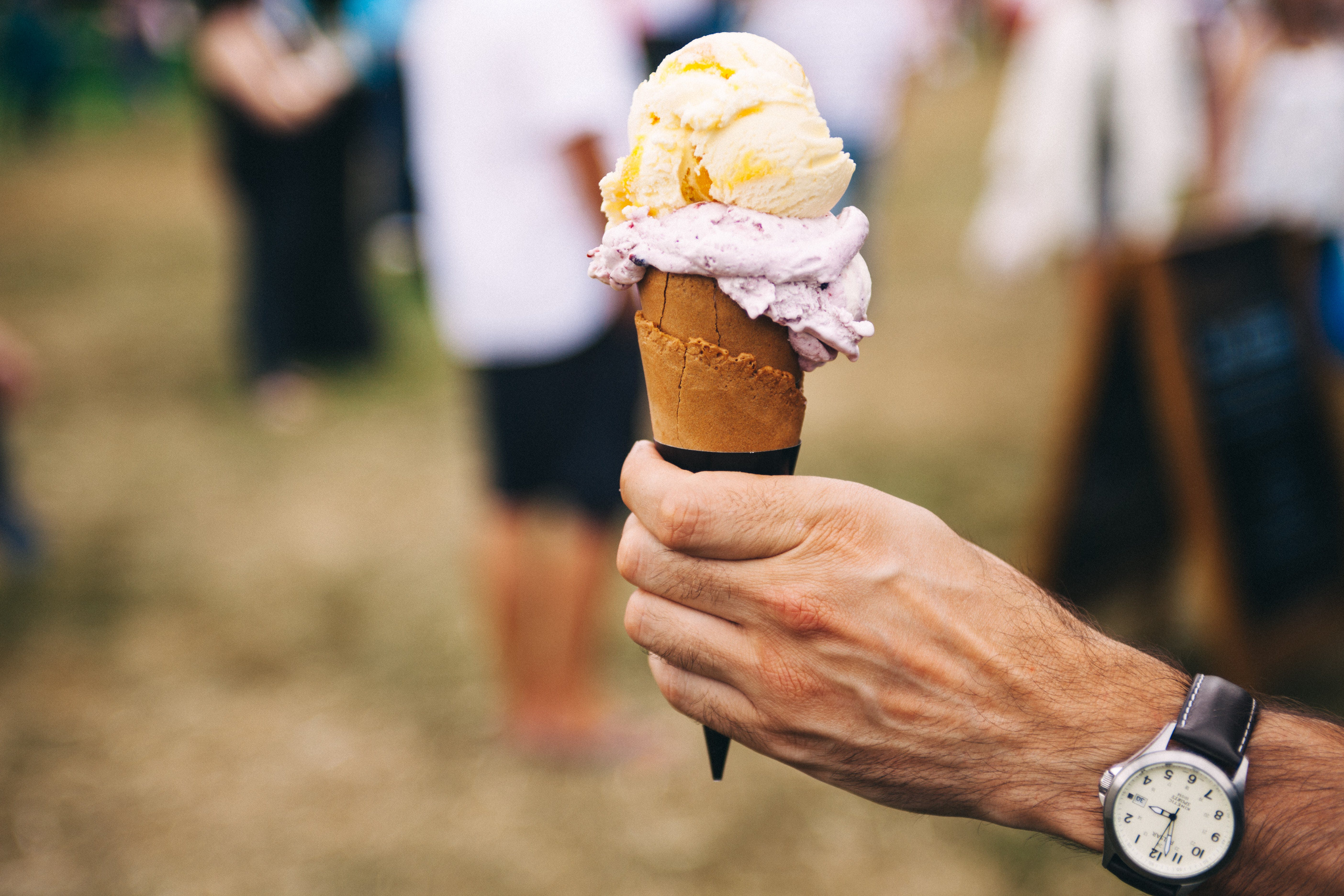 Person Holding Yellow and Purple Ice Cream