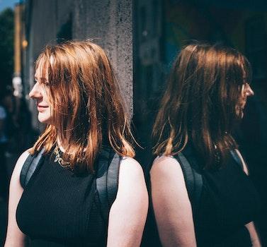 Woman in Black Sleeveless Top Wearing Black Backpack