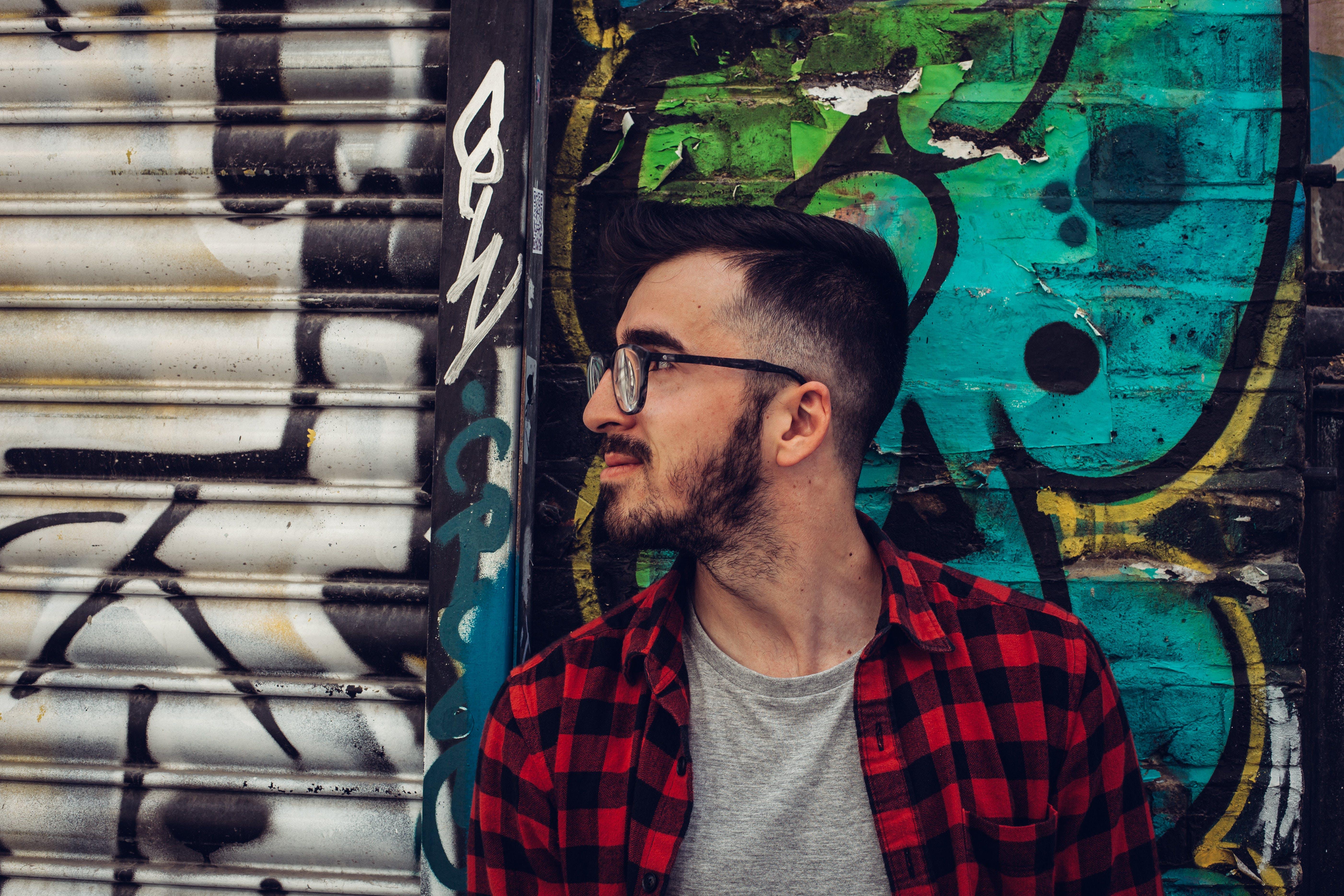 Man Wearing Black Framed Eyeglasses Standing Beside Blue and Black Wall