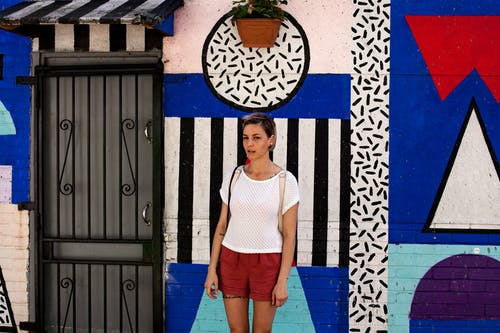 Woman in White Top Standing Near Painted Wall