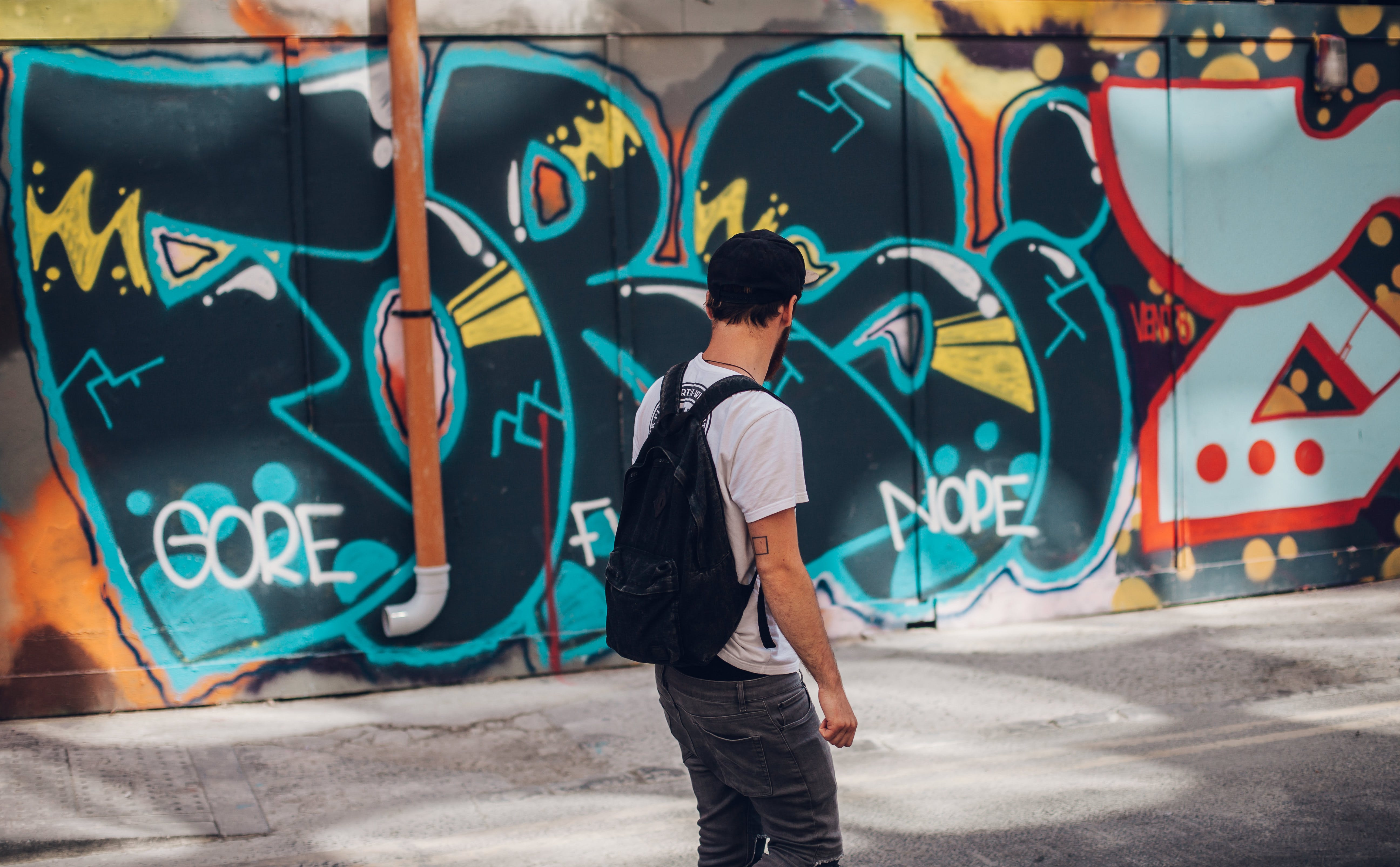 Man Wearing Backpack Near Graffiti Wall