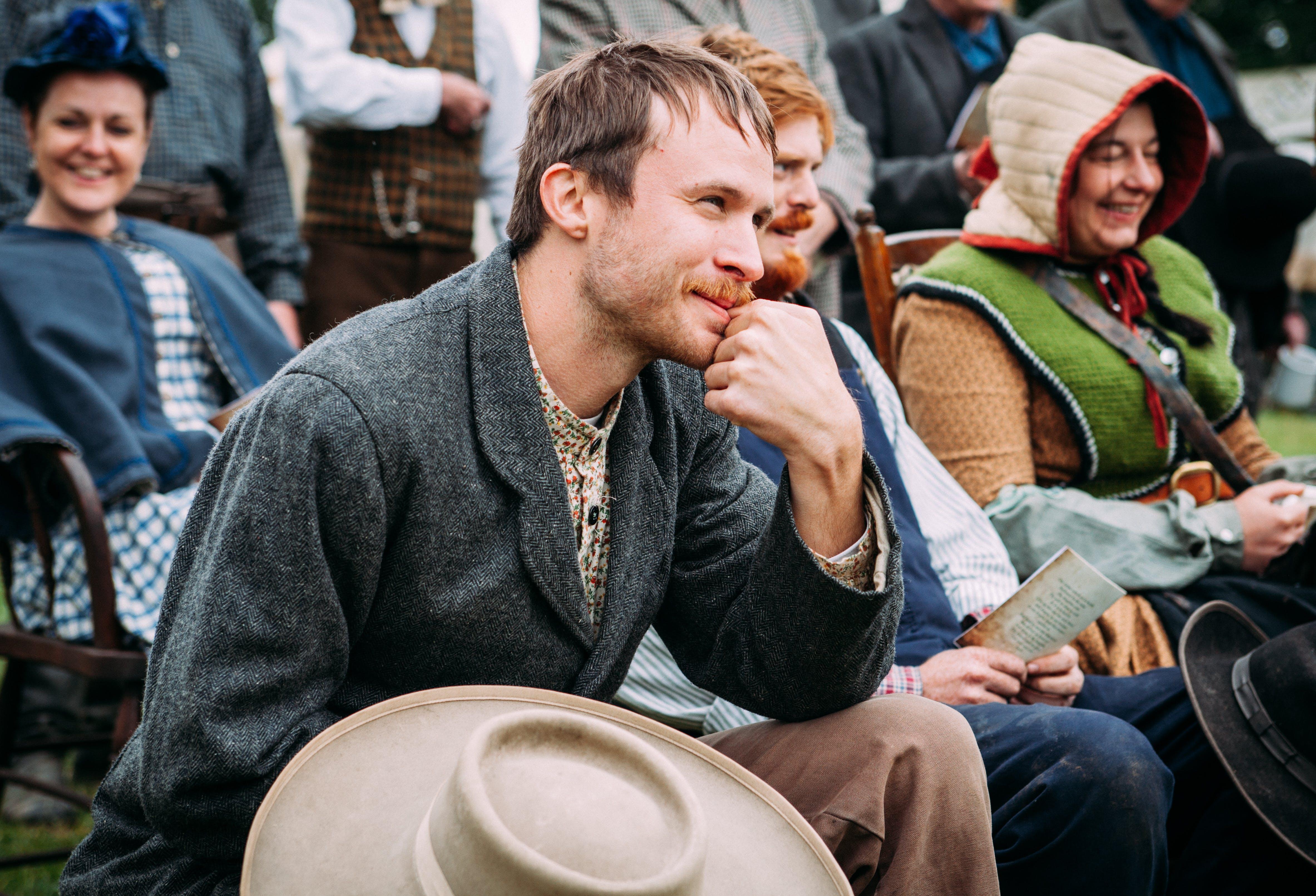 Man Wearing Black Jacket Sitting While Smiling