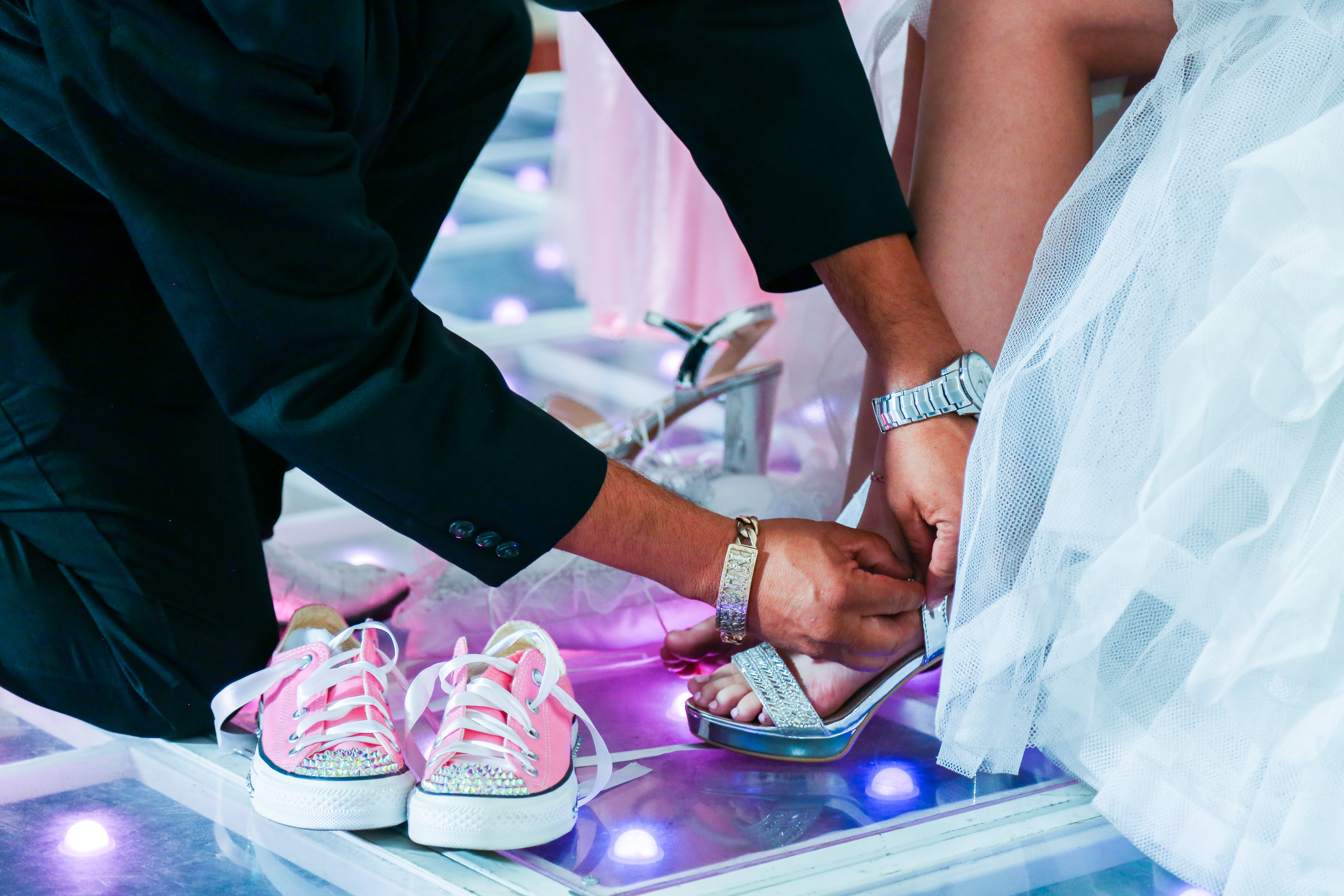 Close-up Photo of Groom Fixing Brides Shoe Strap