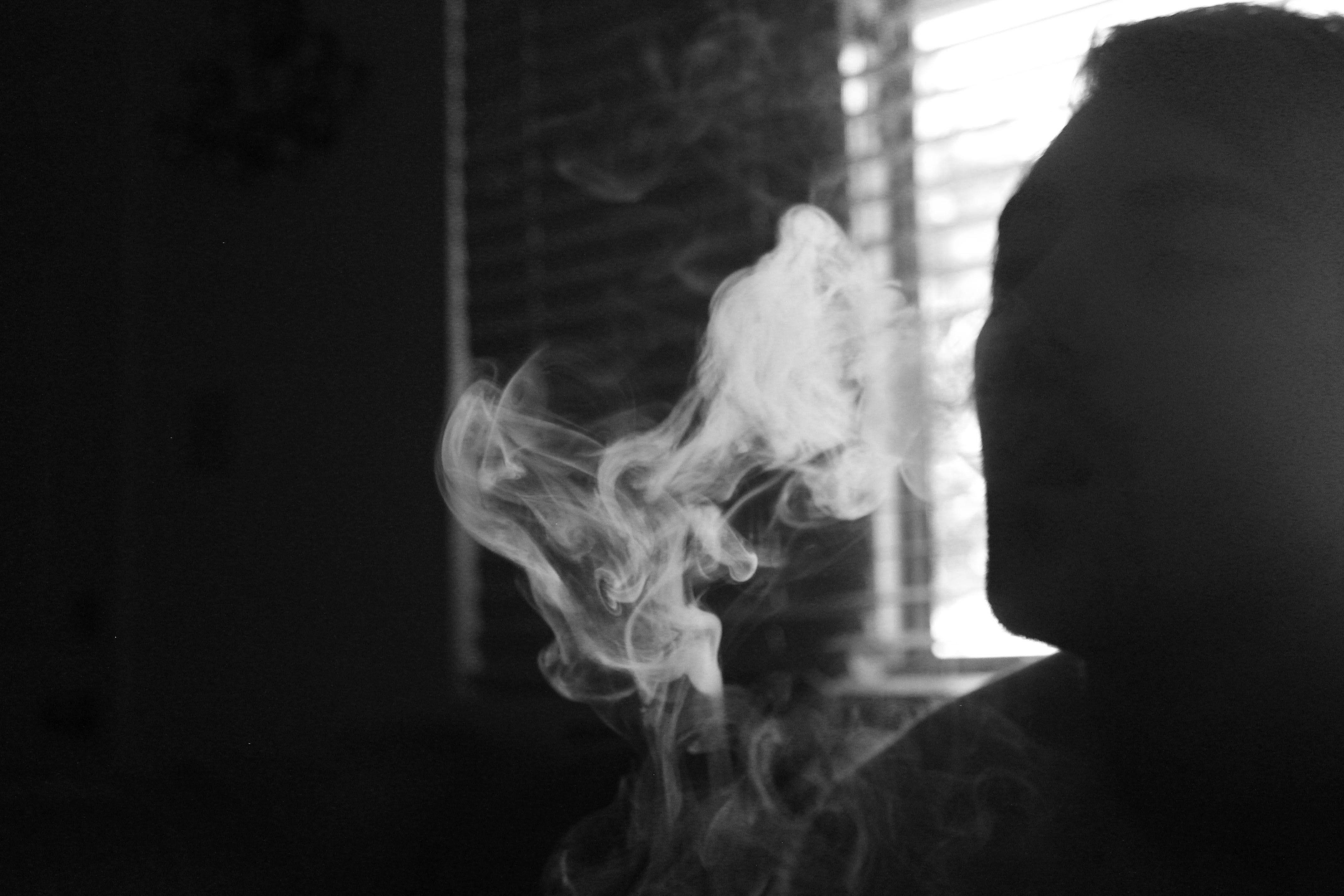 Gray Scale Photo of Human Smoking Inside the Room