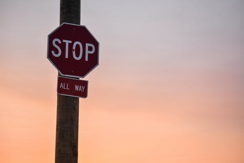 Stop Signage Under Orange Sky