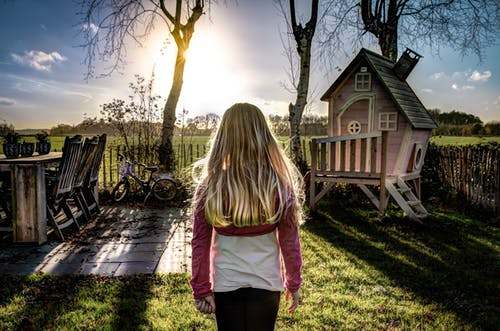 Photography of Girl Standing in Front of Brown Playhouse