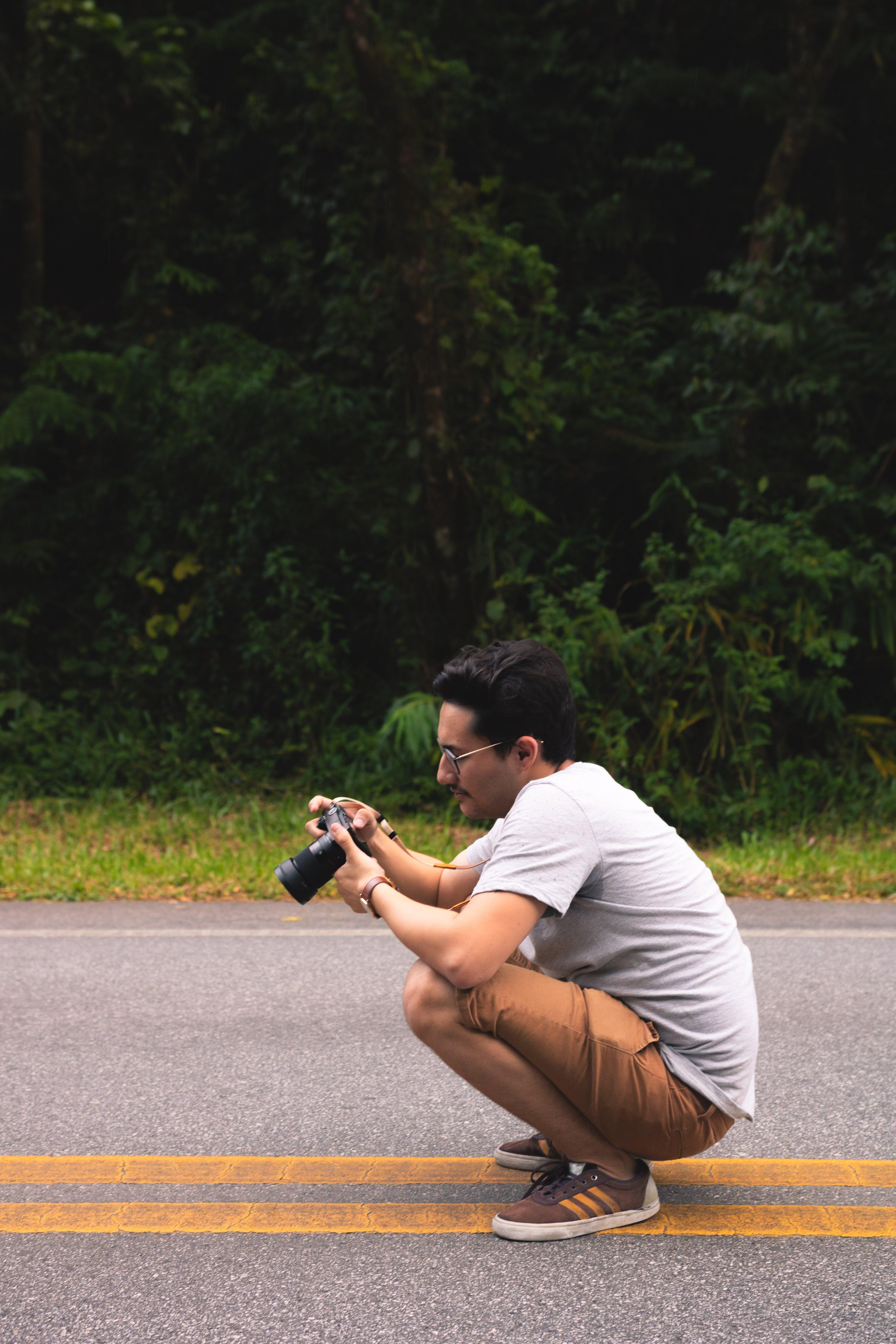 Man Holding Dslr Camera on Road