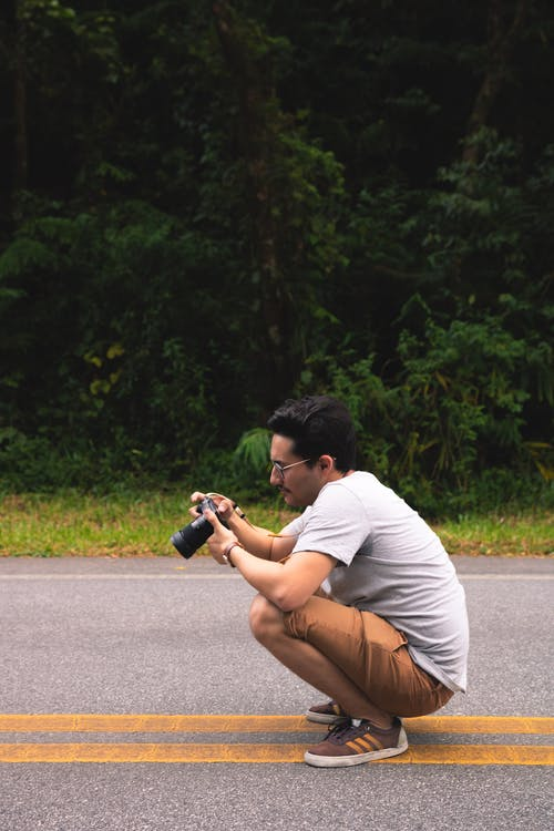 Man Holding Dslr Camera on Road