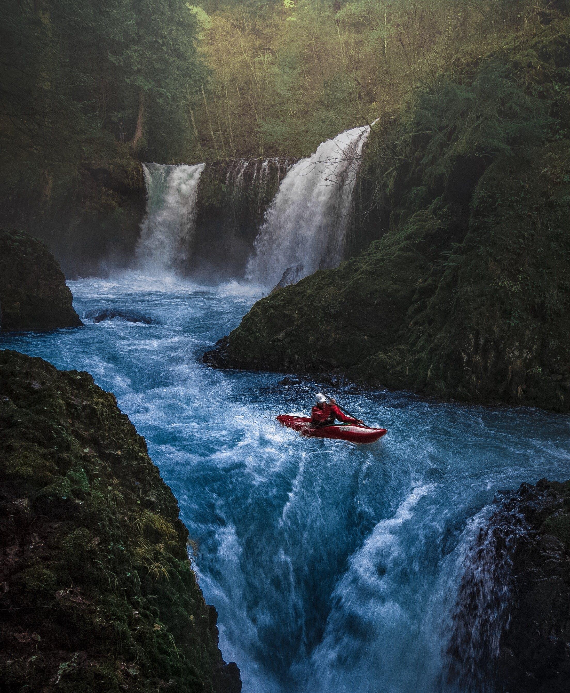 Person on Watercraft Near Waterfall