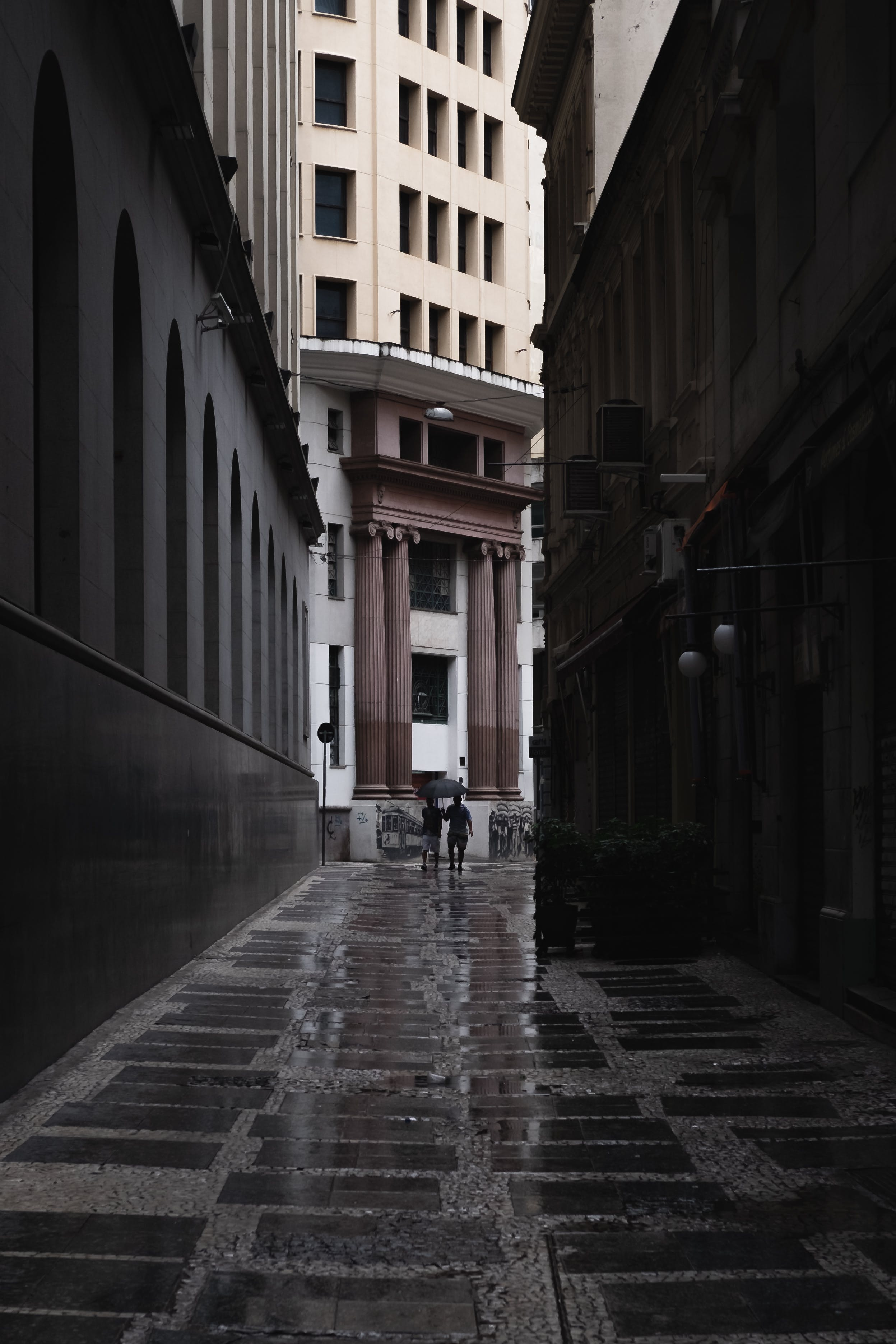 Man Walking Between Buildings