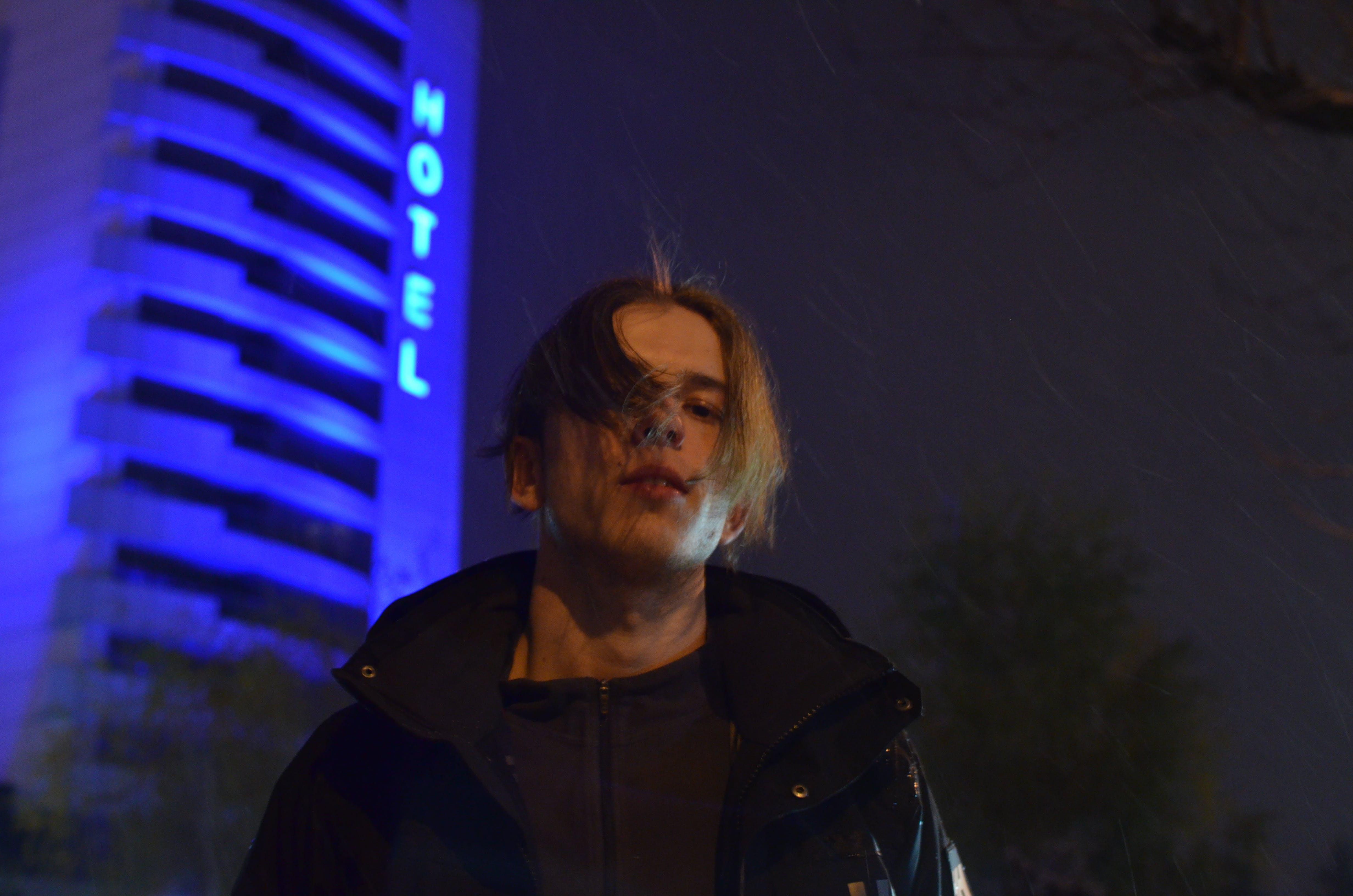Man Wearing Black Zip-up Jacket in Front of Grey Hotel