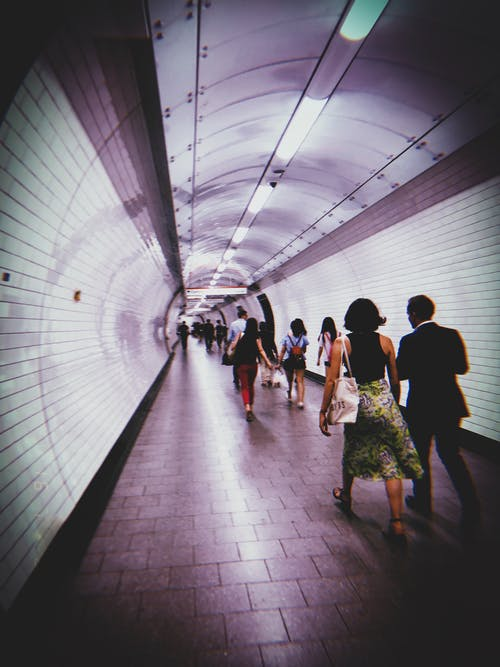 Group of People Walking Down the Train Hallway