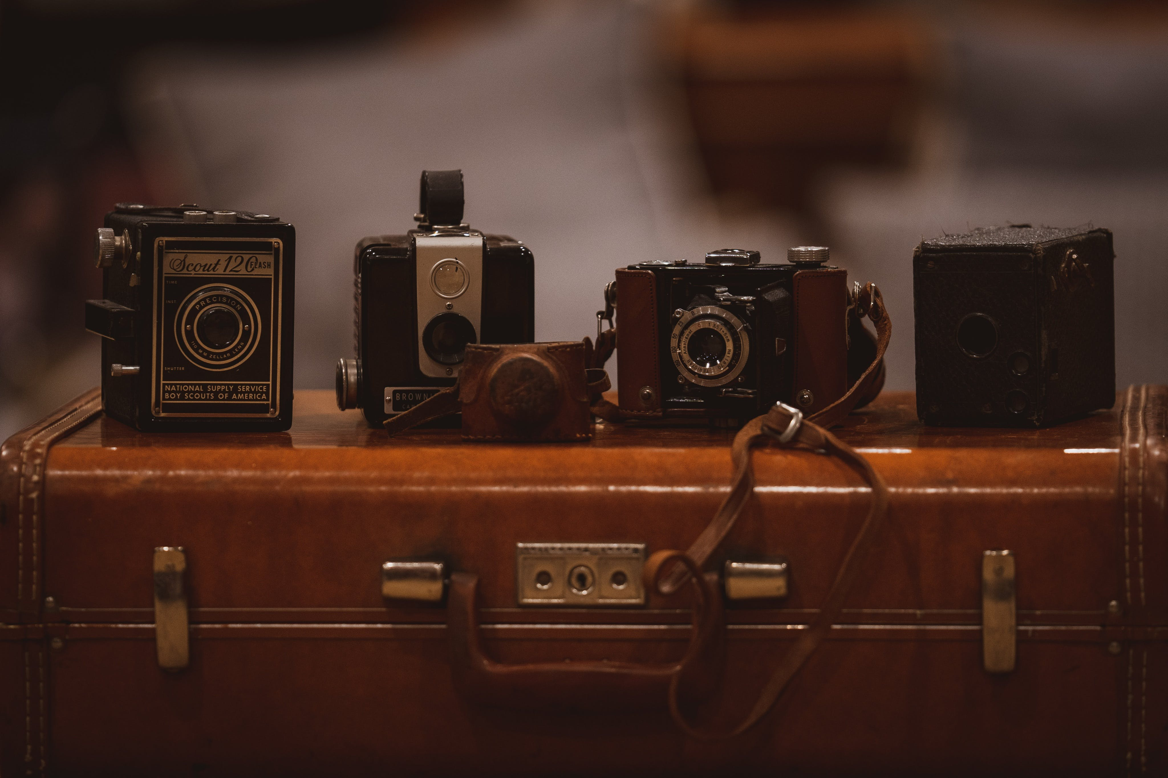 Four Assorted-color Cameras on Brown Suitfcase