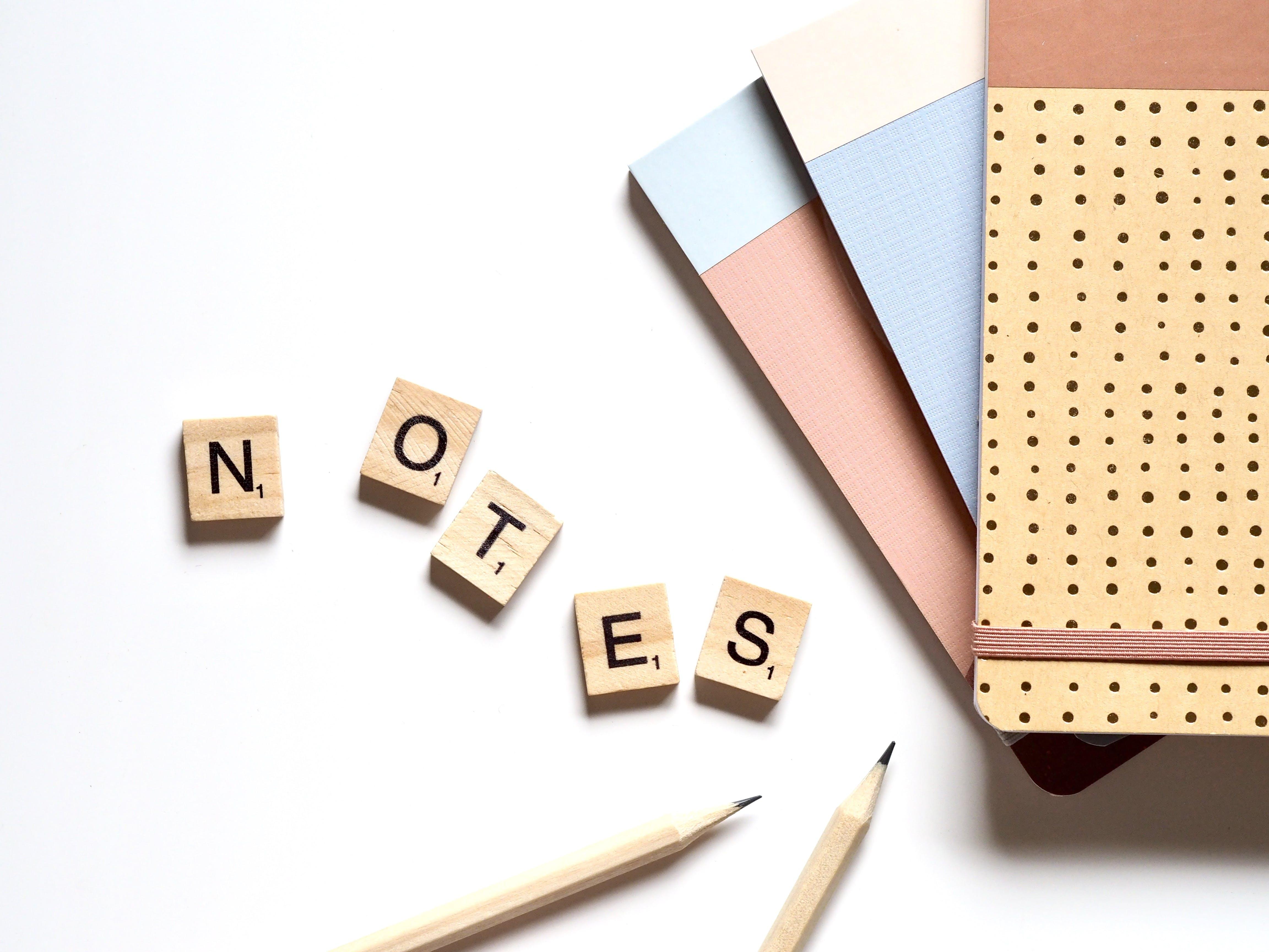 Five Brown Wooden Scrabble Tiles Beside Two Pencils