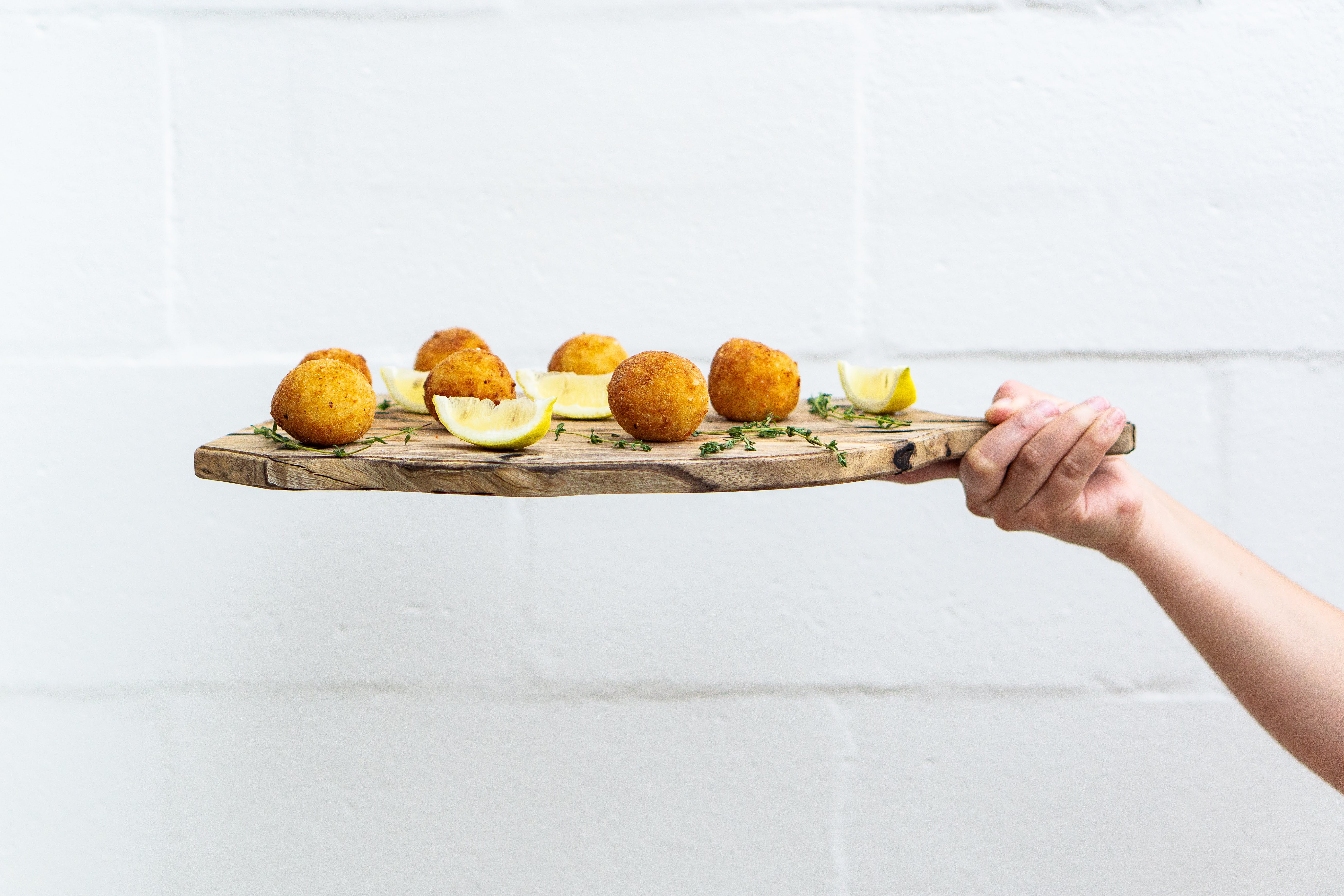 Person Holding Chopping Board With Meatballs and Sliced Lemons
