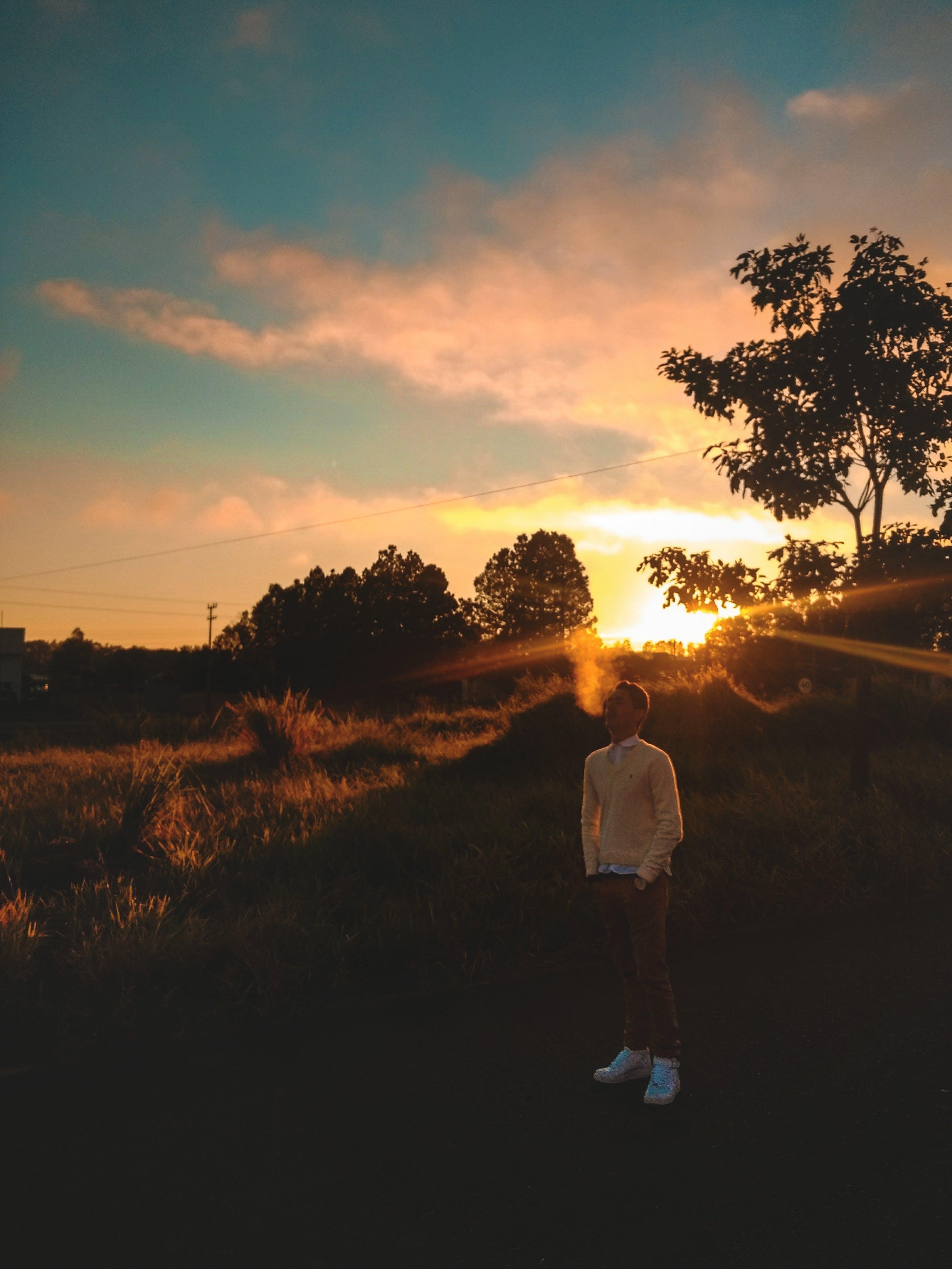 Man Standing On Grass During Golden Hour