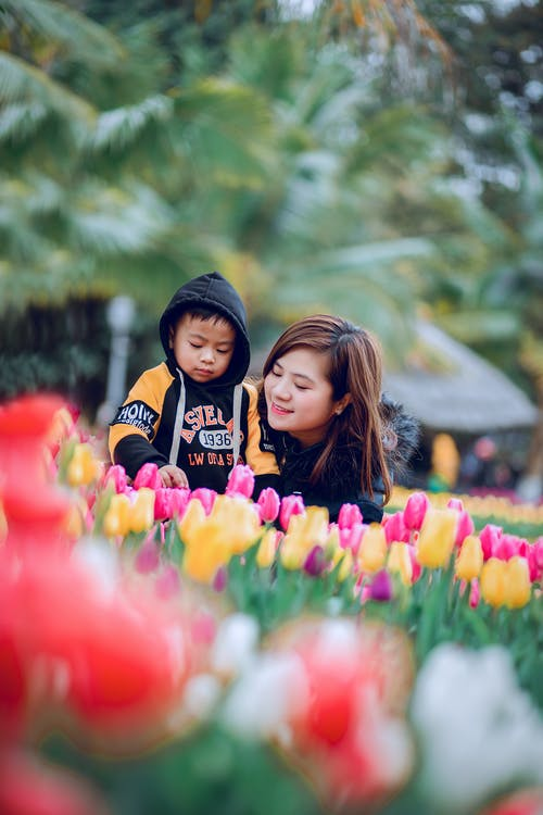 Selective Focus Photography of Woman and Toddler on Flower Bed
