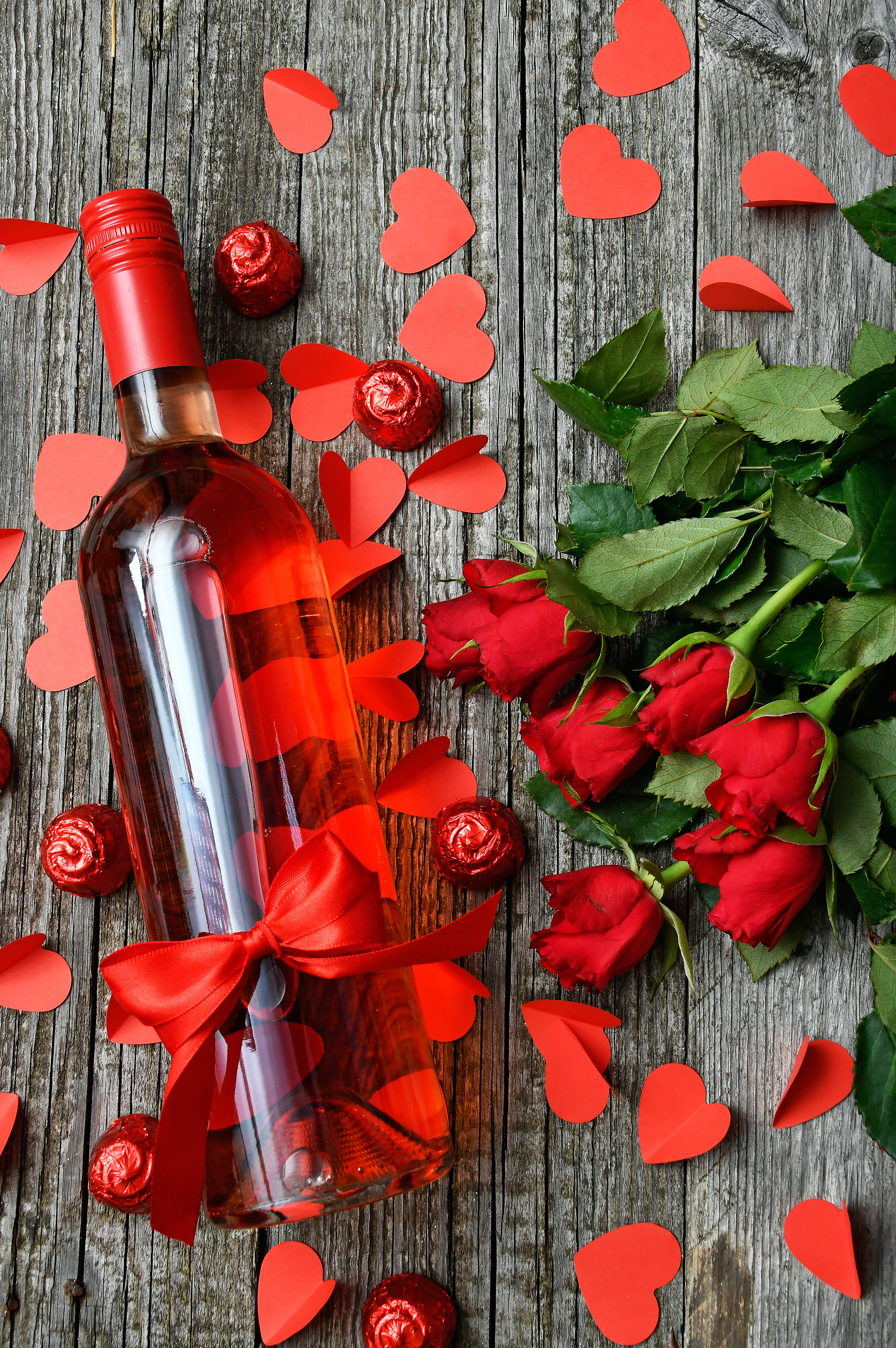 Flatlay Photography Of Glass Bottle And Bunch Of Red Rose Flowers