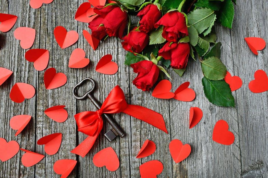 Black metal skeleton key beside red roses bouquet on gray surface