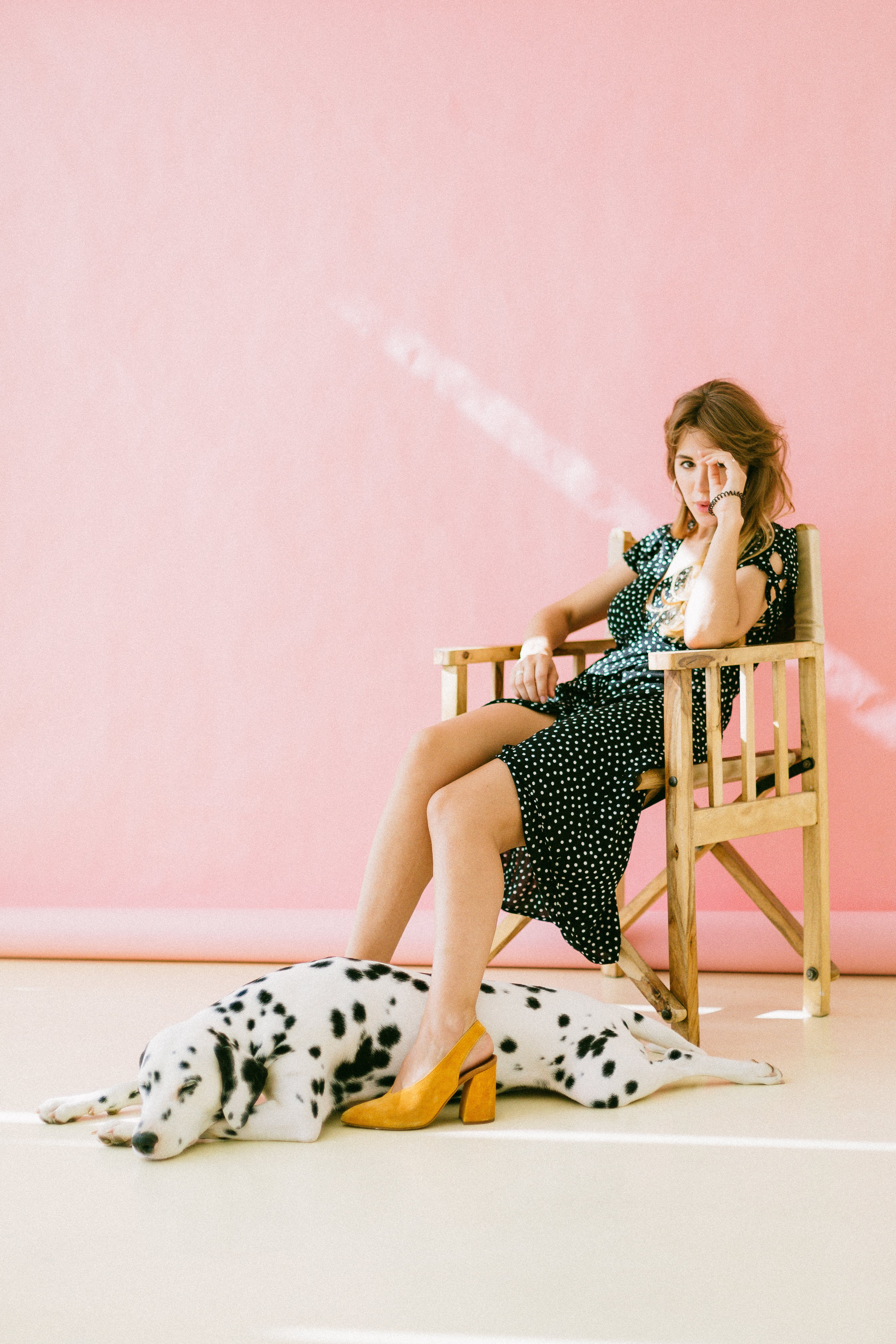 Woman Sitting On Chair With Dalmatian