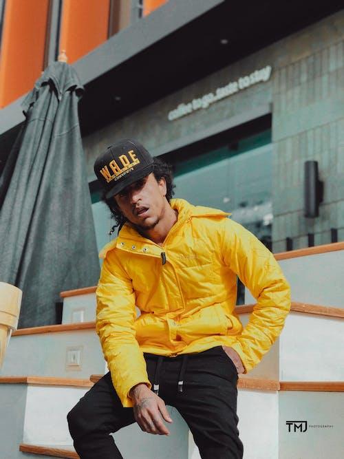 Man Wearing Cap and Yellow Jacket Taking Selfie