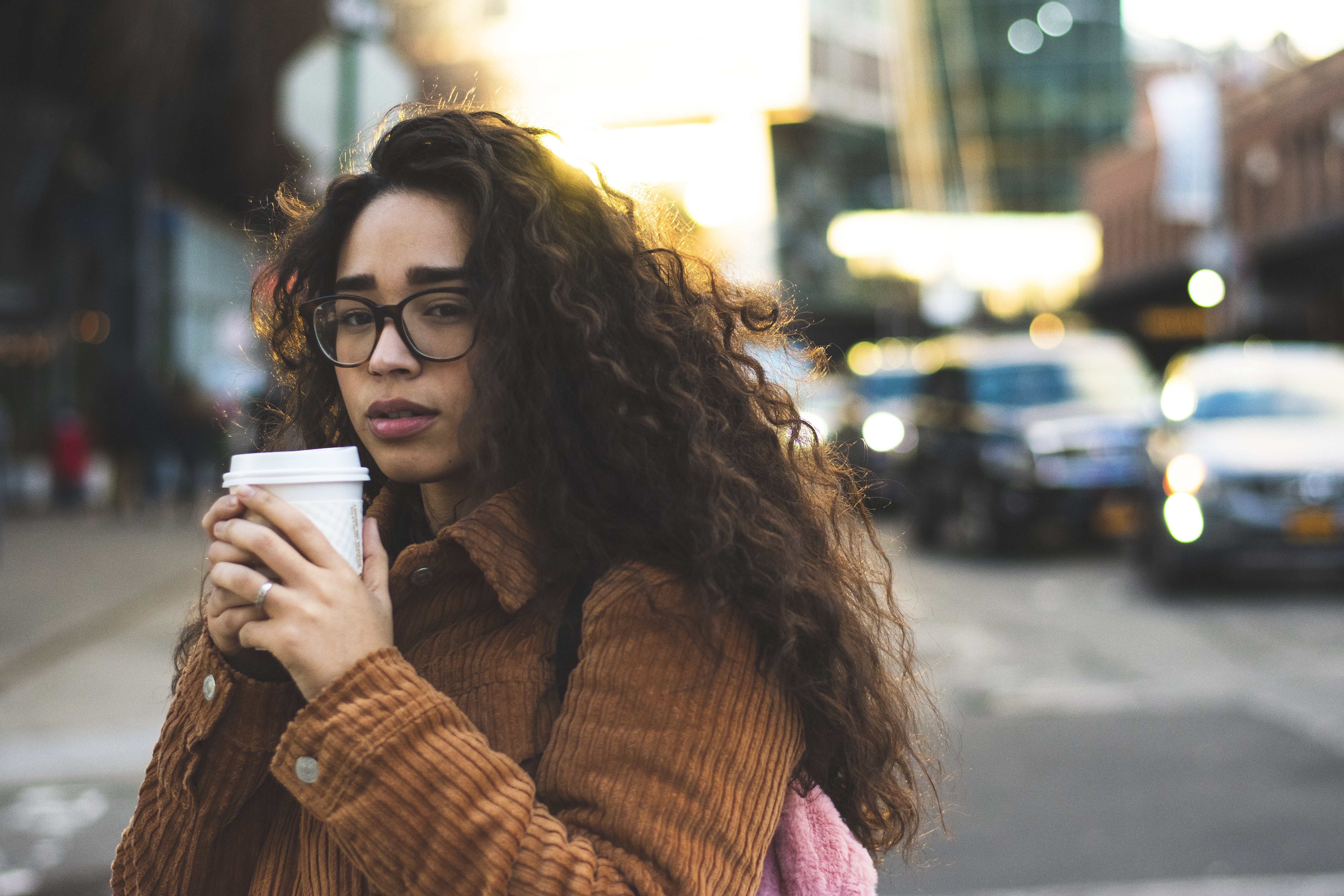 Selective Focus Photography of Woman Holding Disposable Cup