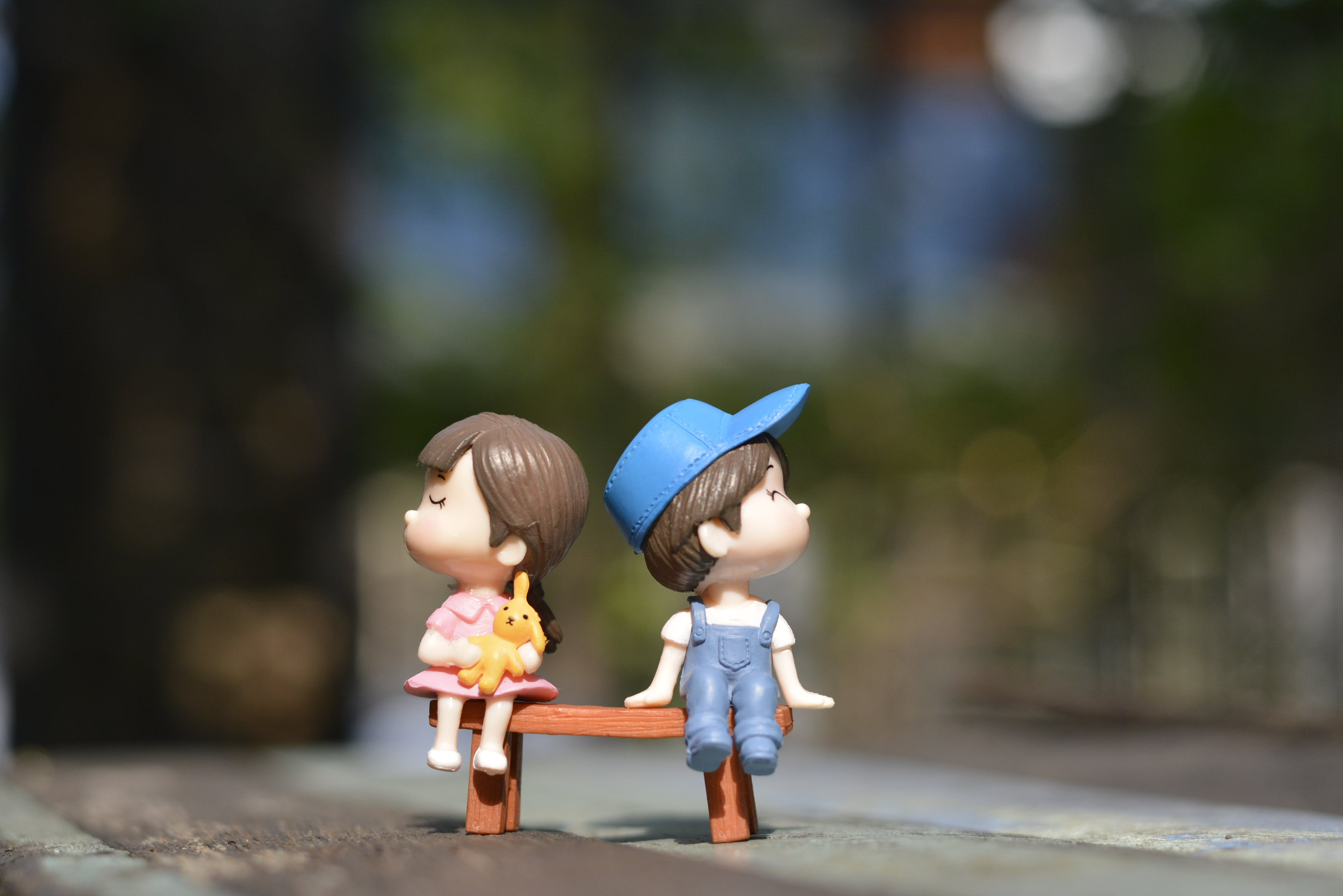 Boy and Girl Sitting on Bench Toy